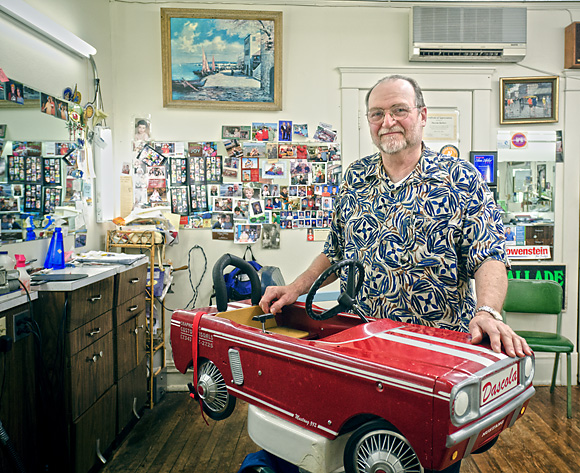 Bob Dascola pictured with what you can see in the background as what he likes to call his 'happy mirror' covered with the photos of his long-term customers, family Christmas cards and so on.
