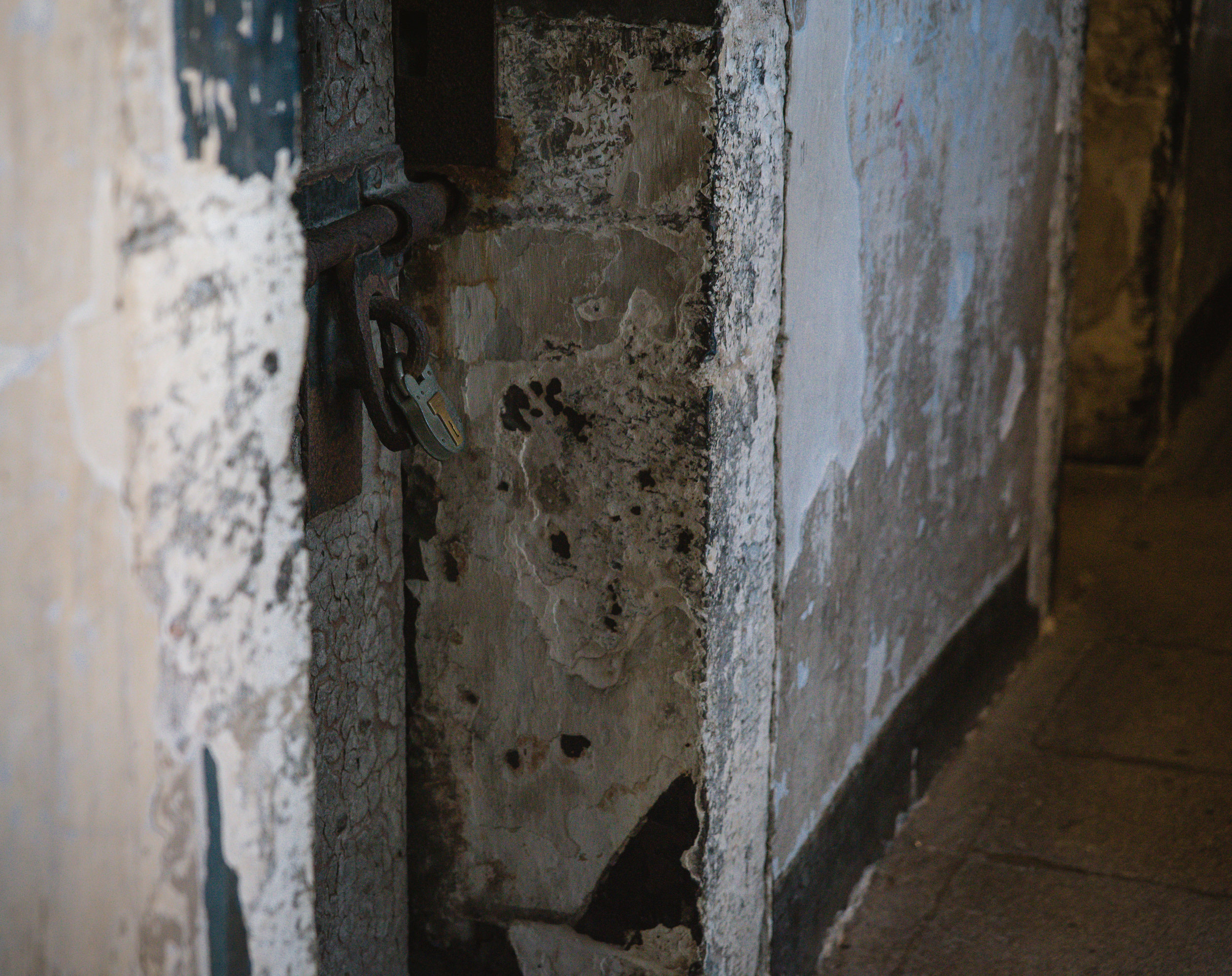 A lock rests on the door of one of the cells.