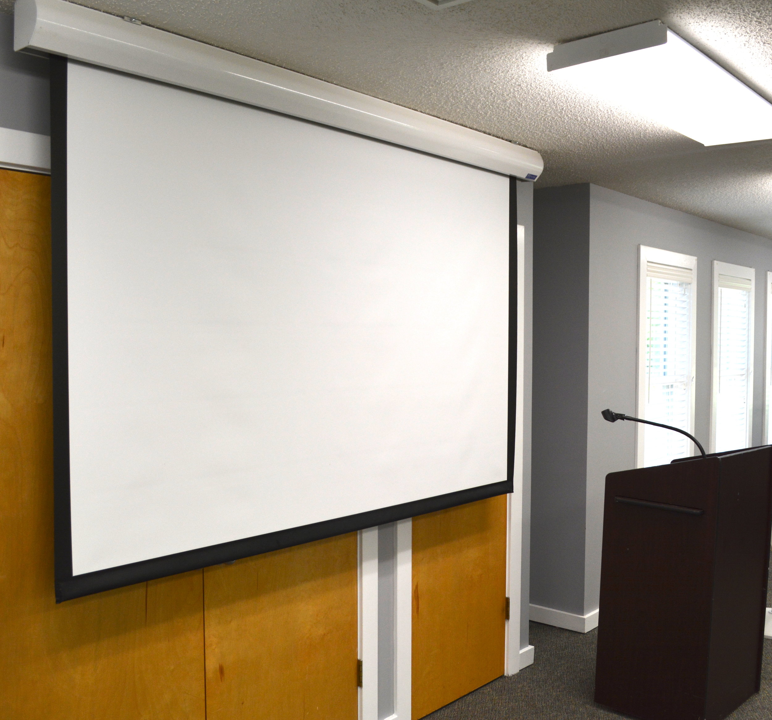 There is a large screen and a podium in the main room. The switch to lower and raise the screen is on the wall over the audio control box.