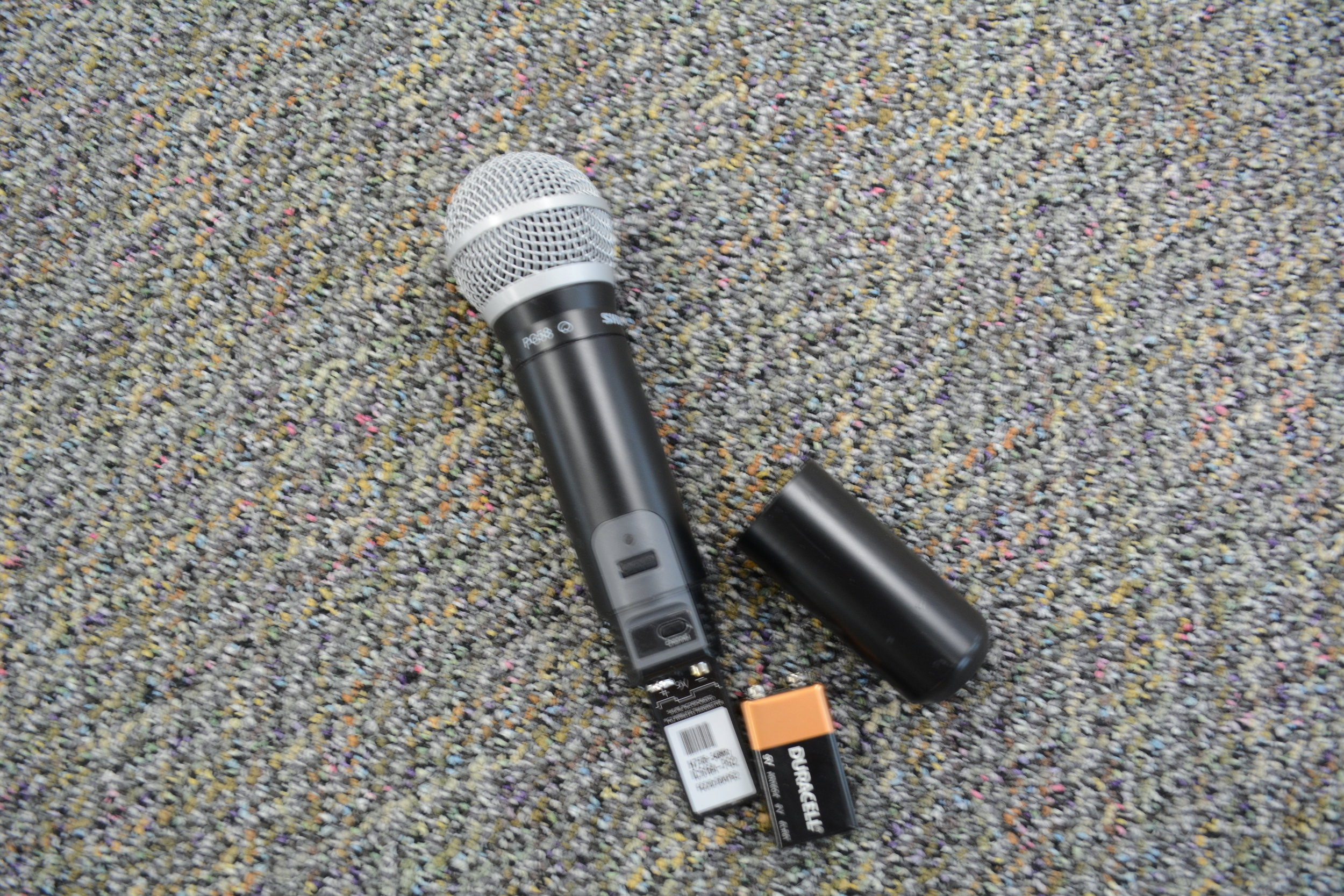 Both a wireless microphone and the wired microphone are in the wall-mounted metal box with the audio equipment in the main room.  If the wireless microphone does not seem to work, unscrew the bottom cover to access the battery and make certain the battery is connected. Spare 9-Volt batteries can be found in the audio control box. Also check the settings on the amp.