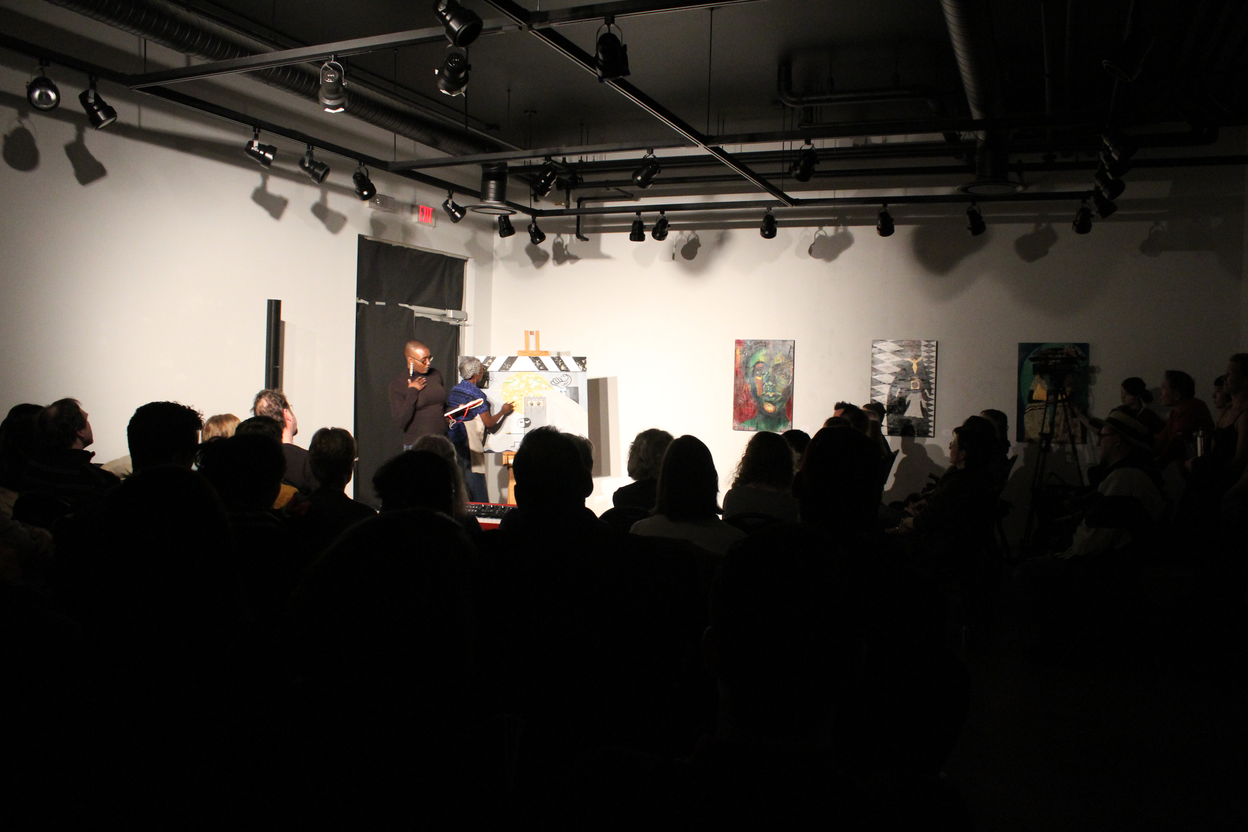 A packed house at the Nina Haggerty Art Gallery watch as mother-daughter duo Elsa and Shima Robinson perform a collaborative piece.