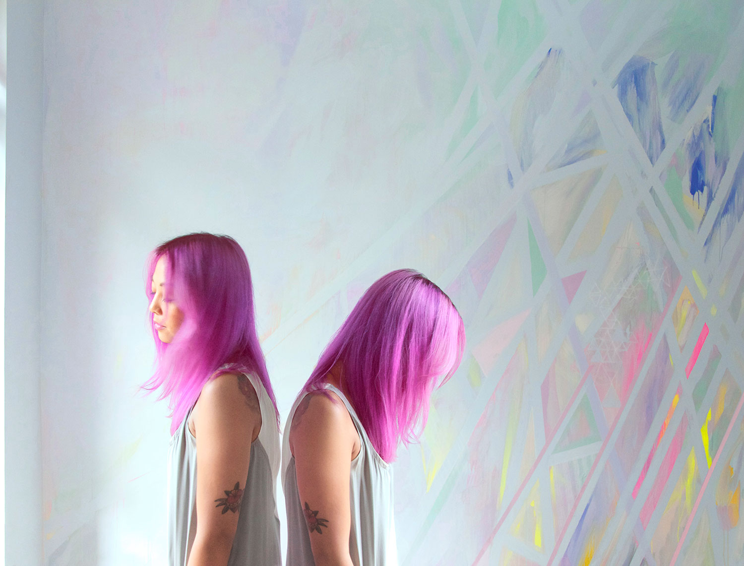 Abstract prism wall art mural painted in pastel colors located in a NYC bedroom, model has pink magenta hair, floral arm tattoo and wears a silk dress.
