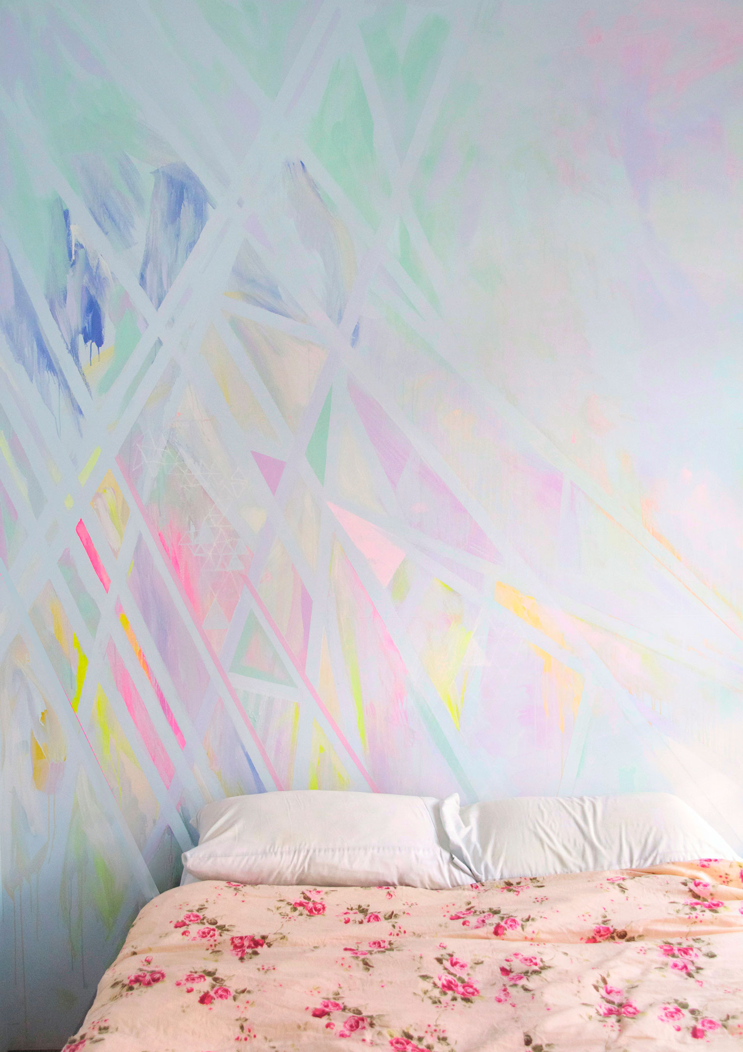 Abstract prism wall art mural painted in pastel colors located in NYC bedroom, styled interior design shoot with floral bedding and blue linen.