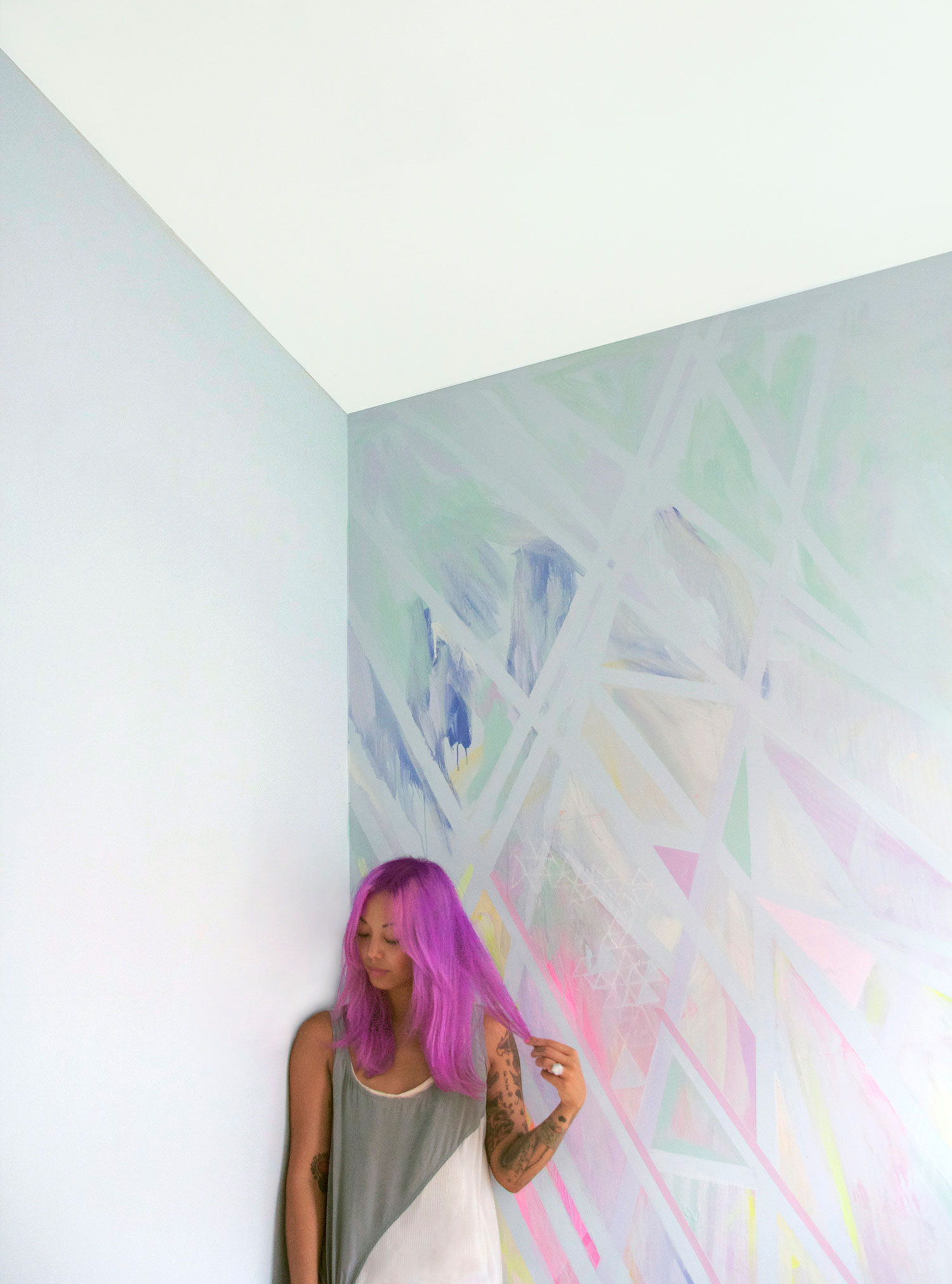 Abstract geometric prism wall art mural painted in pastel colors located in NYC bedroom, styled interior design shoot, model has magenta pink dyed hair, arm tattoos and silk designer dress.