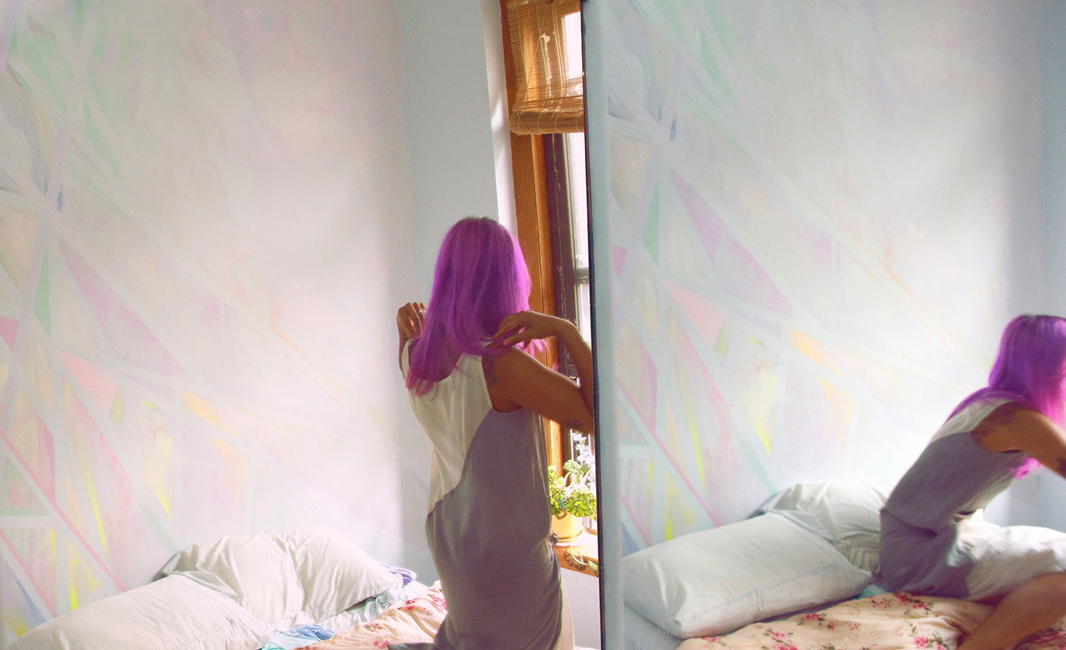 Abstract geometric prism wall art mural painted in pastel colors located in NYC bedroom, styled dreamy interior design shoot with floral bedding, model has magenta pink dyed hair, arm tattoos and silk designer dress.