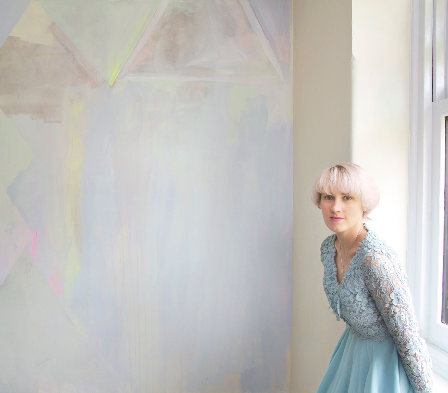 Diamond abstract pastel mural with metallic paint and neon yellow highlights, model has short white blonde hair and stares thoughtfully while wearing pastel blue lace vintage dress.