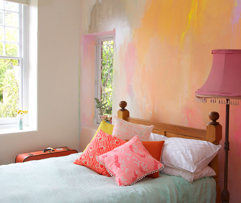 Bright, happy styled bedroom with painted abstract mural in earthy summer colors of peach, coral, yellow and pink, featuring mint bed linen and vintage fabric cushions.