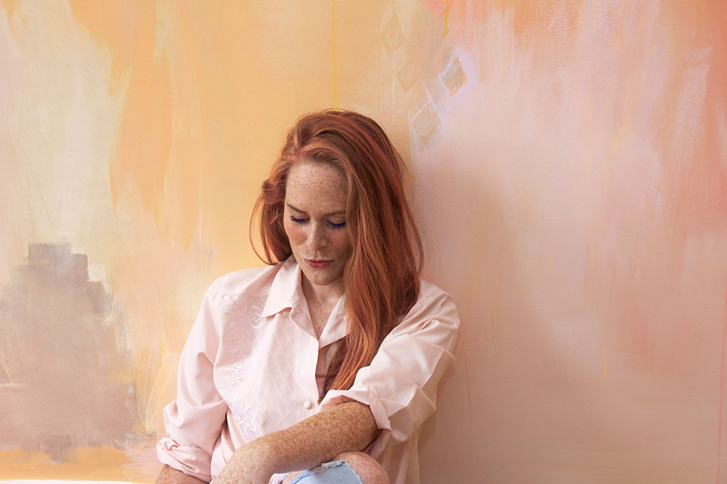 Red haired model leans against bedroom wall wearing pink silk shirt, her freckles match the color of the abstract painted mural.