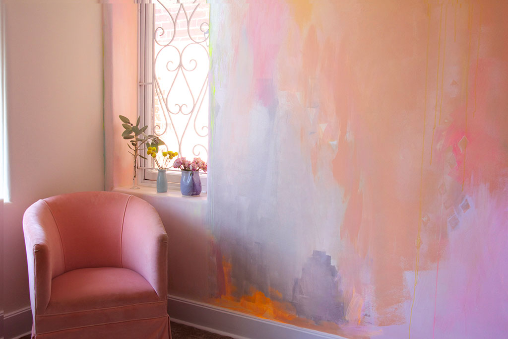 Dreamy, romantic styled bedroom with painted abstract mural features pink velvet vintage arm chair and sweet flowers on the windowsill.