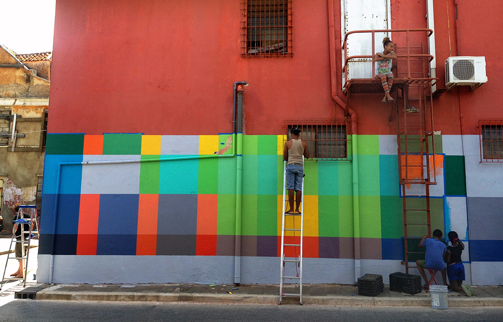 Haas & Hahn community mural project in Curacao, workshop part of Favela Painting Academy, design features brightly colored geometric squares that wrap around the building like woven fabric, kids climb the fire escape and help paint the mural.