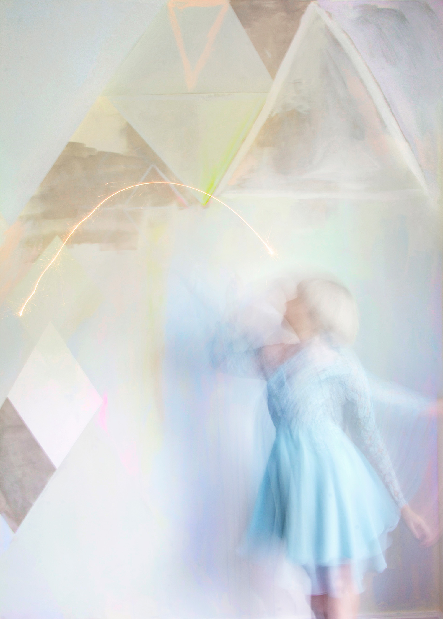 Playfully styled interior dining room with diamond abstract pastel mural featuring model playing with sparklers while wearing baby blue lace vintage dress.