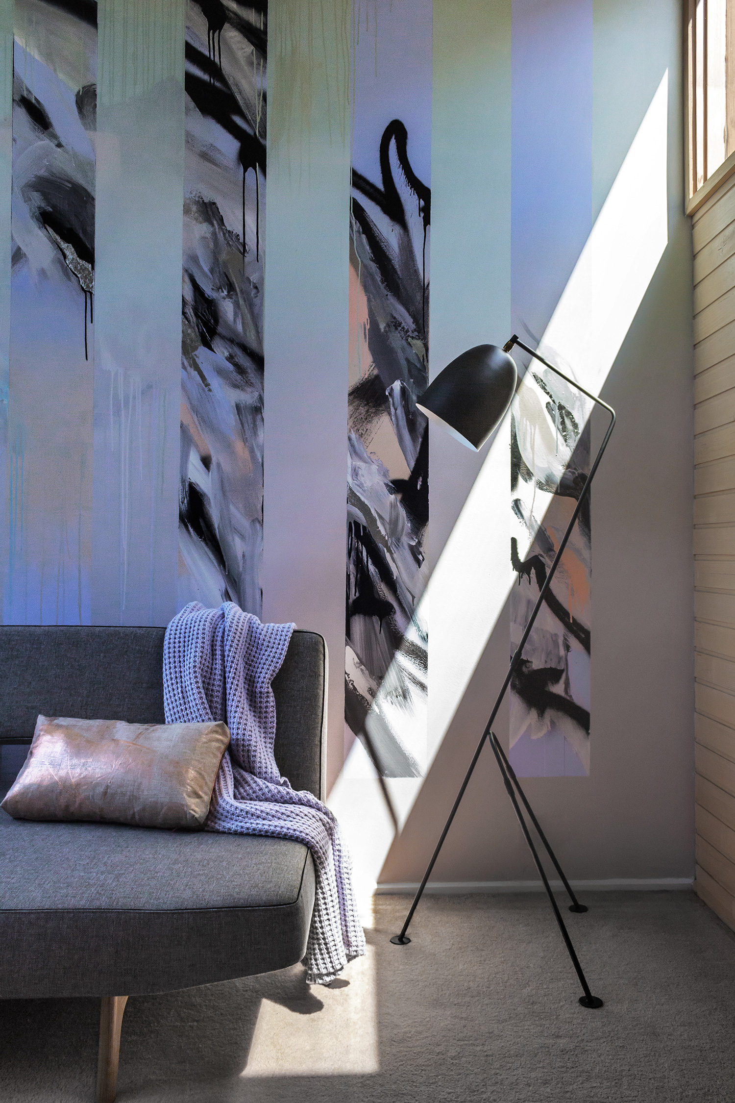Abstract mural in living room painted with black and white and gradient, beautifully styled with a couch by Innovation Living, metallic cushion, contemporary black lamp and lavender blanket.