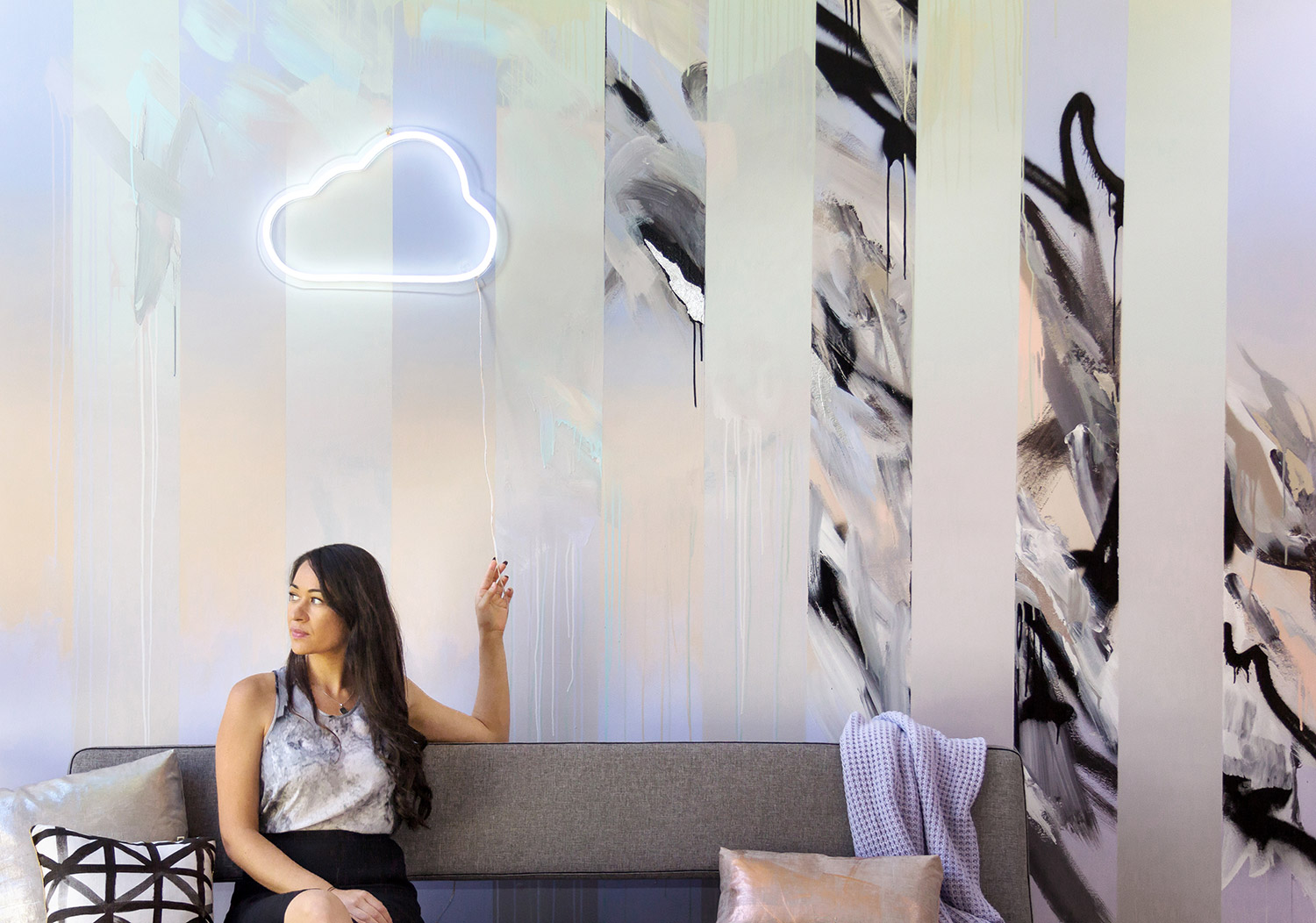 Abstract mural in living room with silver leaf and gradient, beautifully styled with a couch by Innovation Living, Bonnie and Neil cushion, metallic cushions and neon LED cloud sign by Neon Poodle, model where's marble silk top and has long black hair.