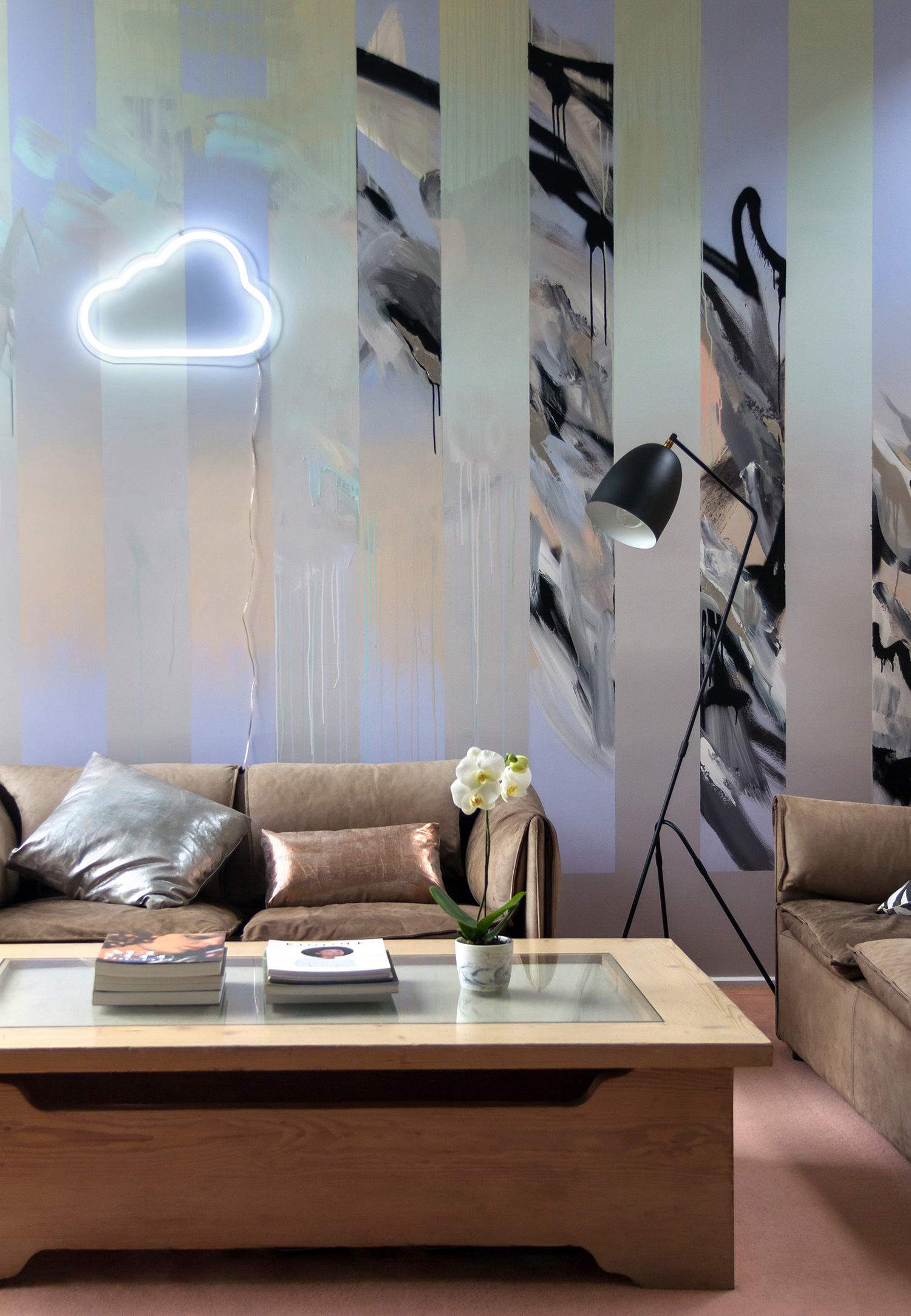 Abstract mural in living room painted with black and white and gradient, beautifully styled with brown vintage leather couches, metallic silver and copper cushions, contemporary black lamp and orchid in marble plant holder.