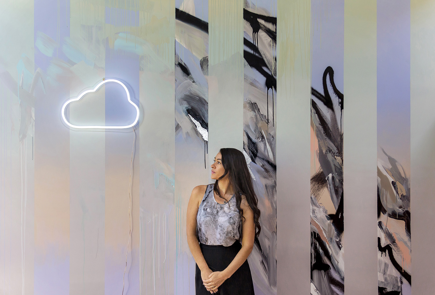 Model with long wavy black hair gazes at the clouds wearing marble silk top and high waist modern skirt, behind her is an abstract painted wall mural, beautifully styled with an LED neon cloud sign.