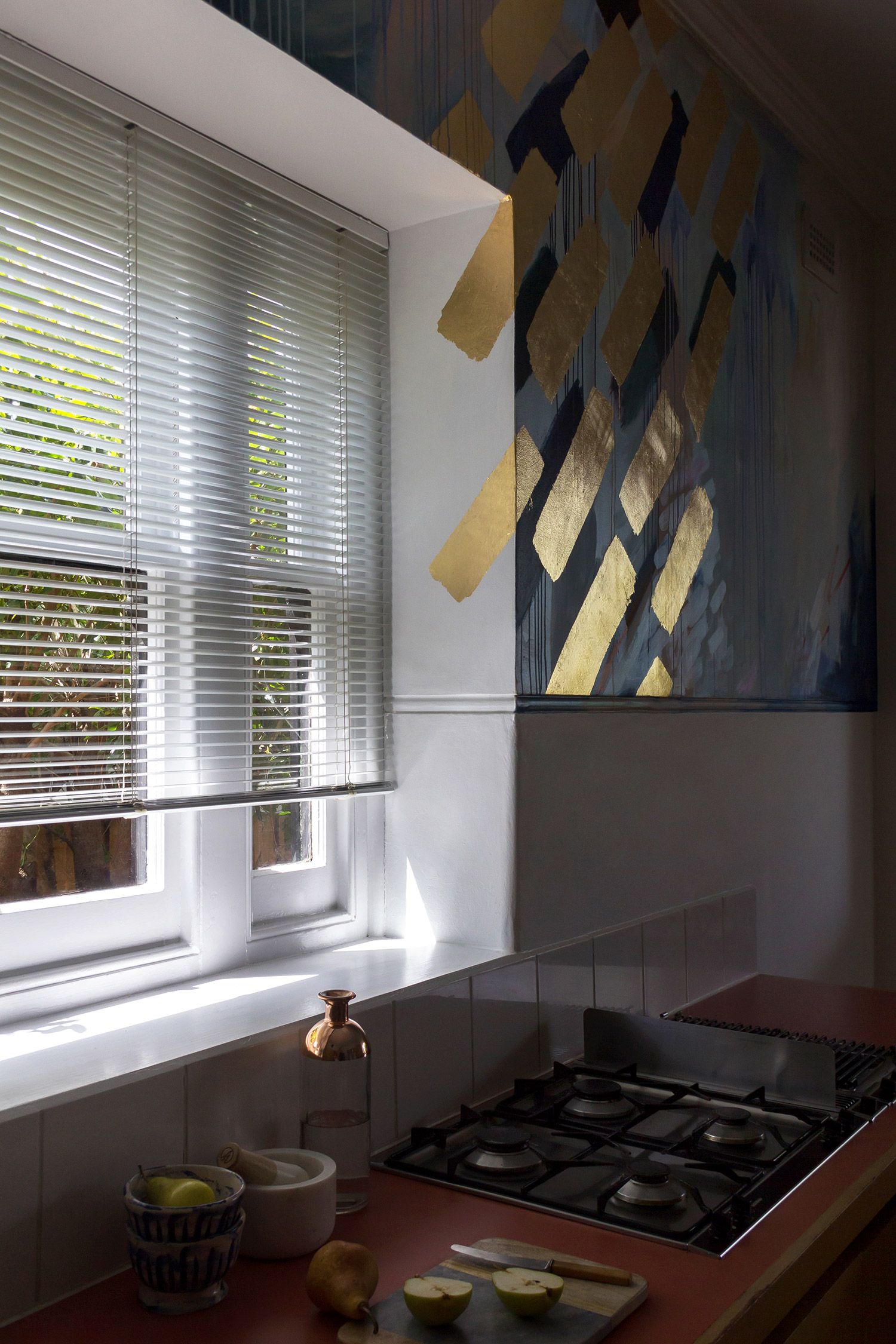Modern, minimal, clean styled kitchen featuring gorgeous abstract mural with gold leaf geometric shapes illuminated by the sun, contemporary and fresh feel, fruit still life on bench.