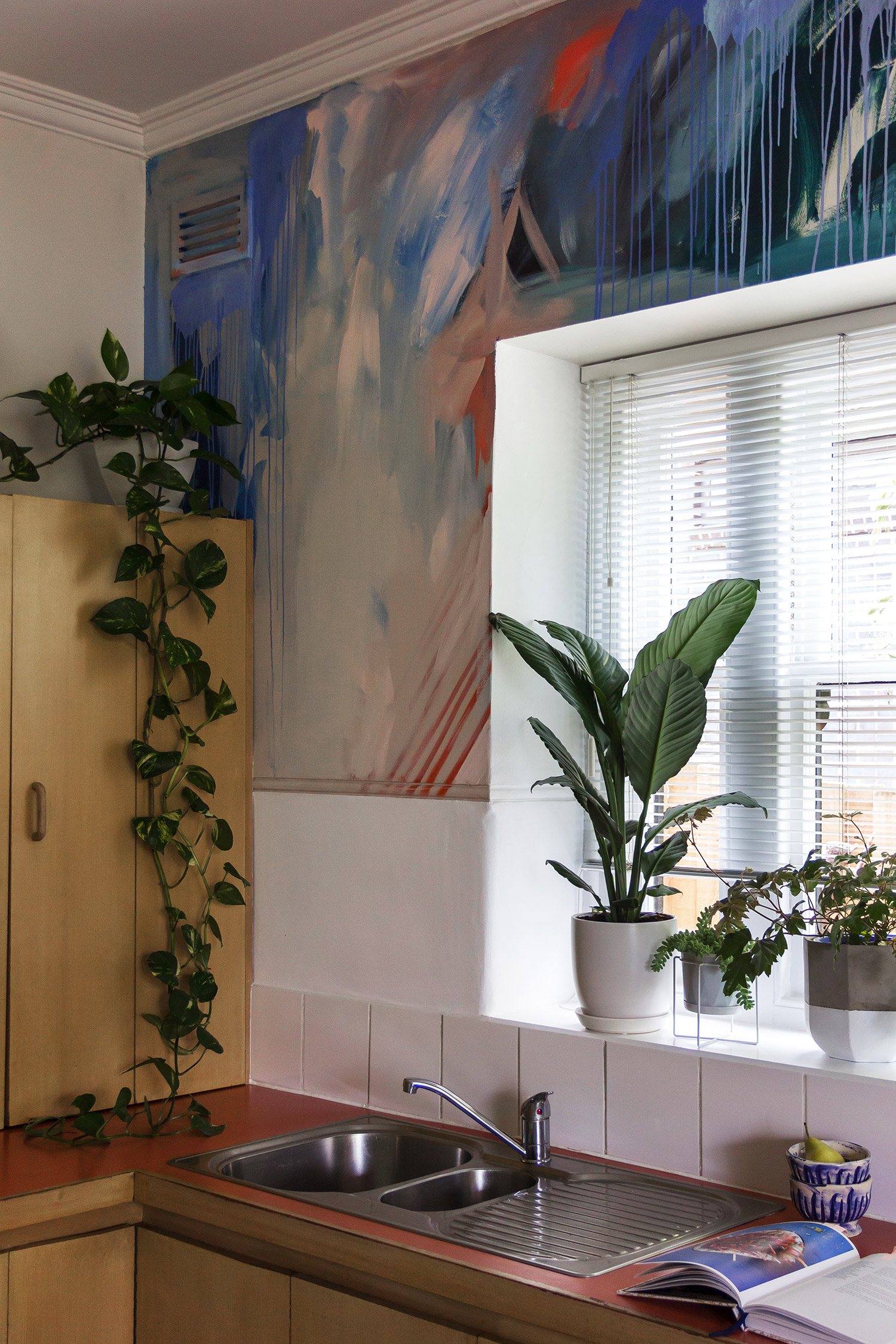 Modern, clean styled kitchen featuring gorgeous abstract mural, contemporary and fresh feel with green plants on windowsill and hanging ivy plant.