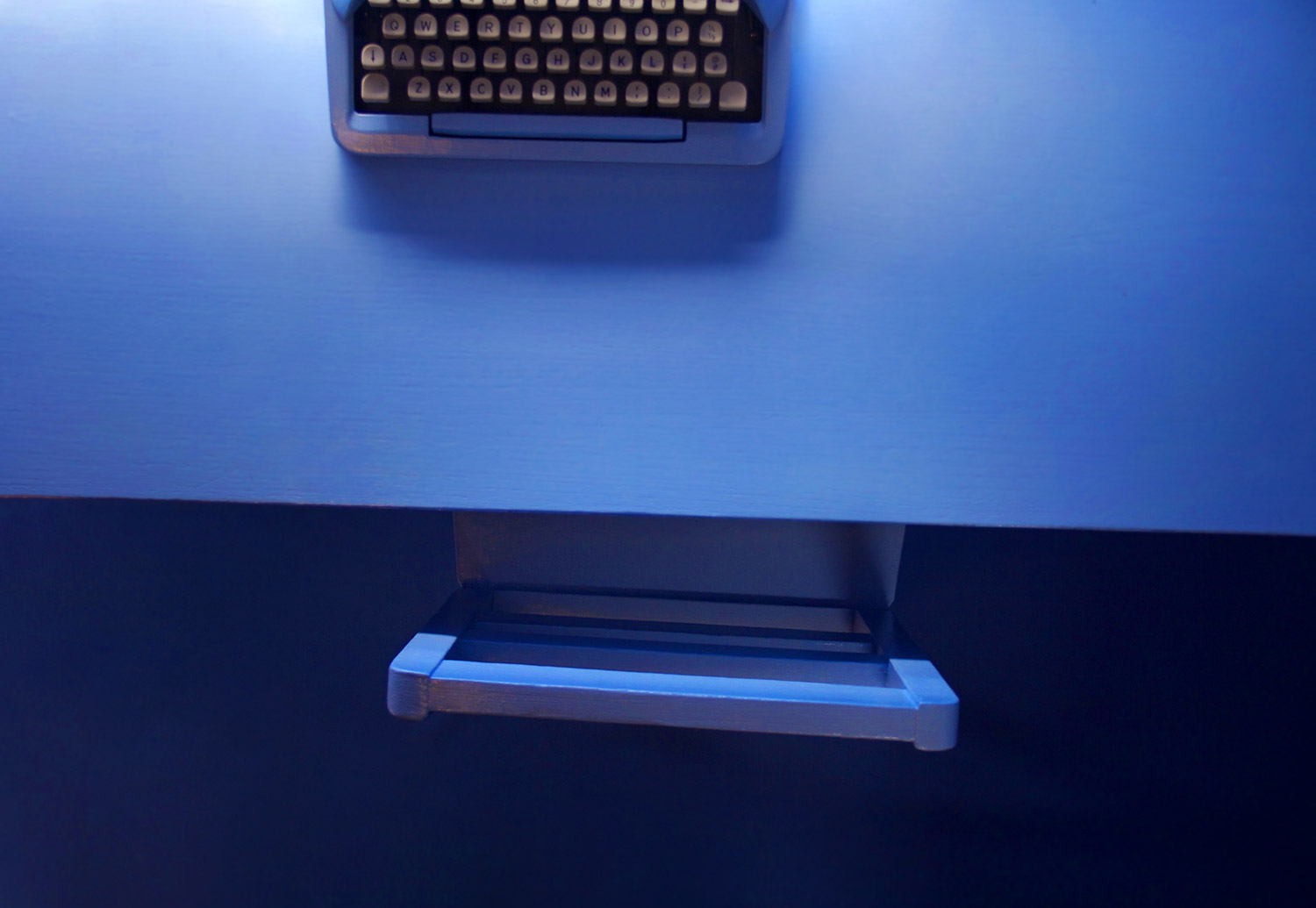 Birds eye view of desk, installation art piece Dream Space Blue, an immersive space painted in one color with typewriter, flowers and rainbow stuffed toucan wall feature.