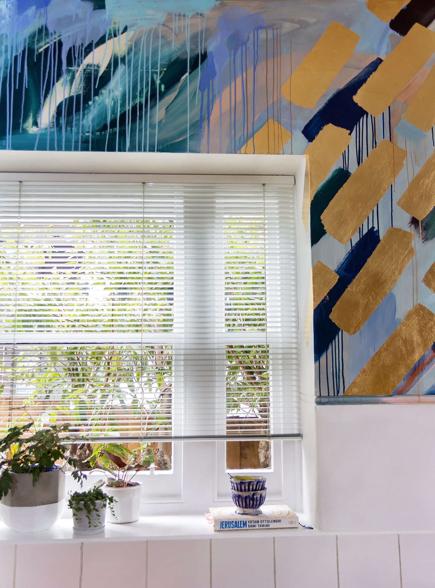 Modern, clean styled kitchen featuring gorgeous abstract mural with gold leaf and painterly drips, contemporary and fresh feel with green plants on windowsill and Jerusalem cookbook.