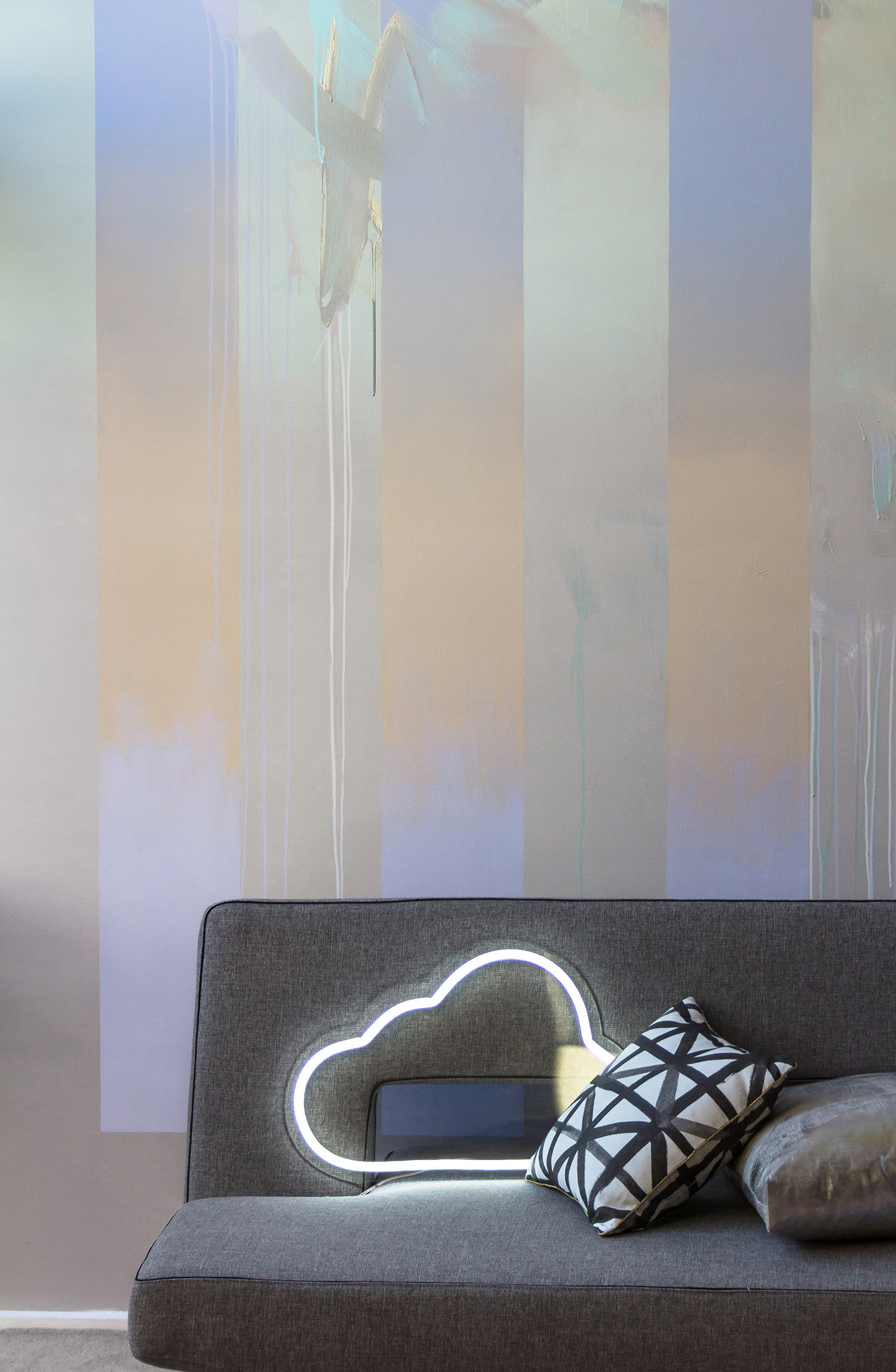 Abstract mural in living room painted in pastels featuring gradient, drips and silver leaf, beautifully styled with a grey sofa bed by Innovation Living, metallic silver cushion, black & white Bonnie & Neil cushion and LED neon cloud sign.
