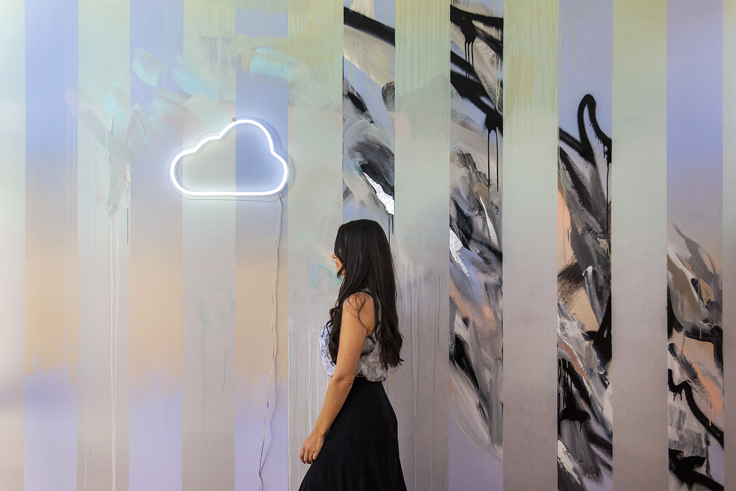 Model with long wavy black hair wears marble silk top and high waist modern skirt, behind her is an abstract painted wall mural, beautifully styled with an LED neon cloud sign.