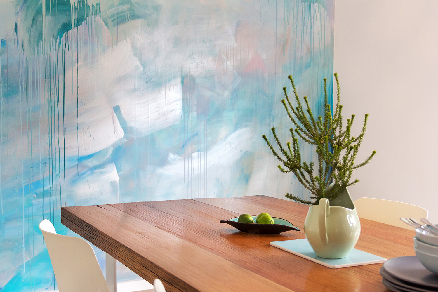 Ocean water painted contemporary abstract mural in kitchen featuring a wave, drips and geometric shapes, the artwork has movement and reflects light.