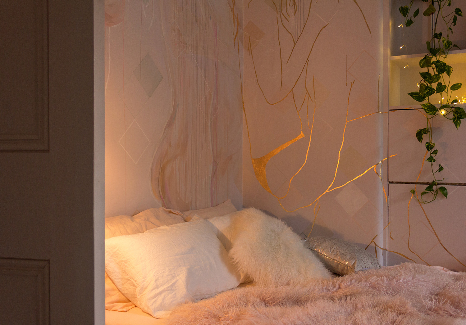 Cosy corner of bedroom mural featuring gold leaf outline of couple in love - male figure holds his girlfriend in his arms.  Ivy plant and fairy lights are styled in the corner.