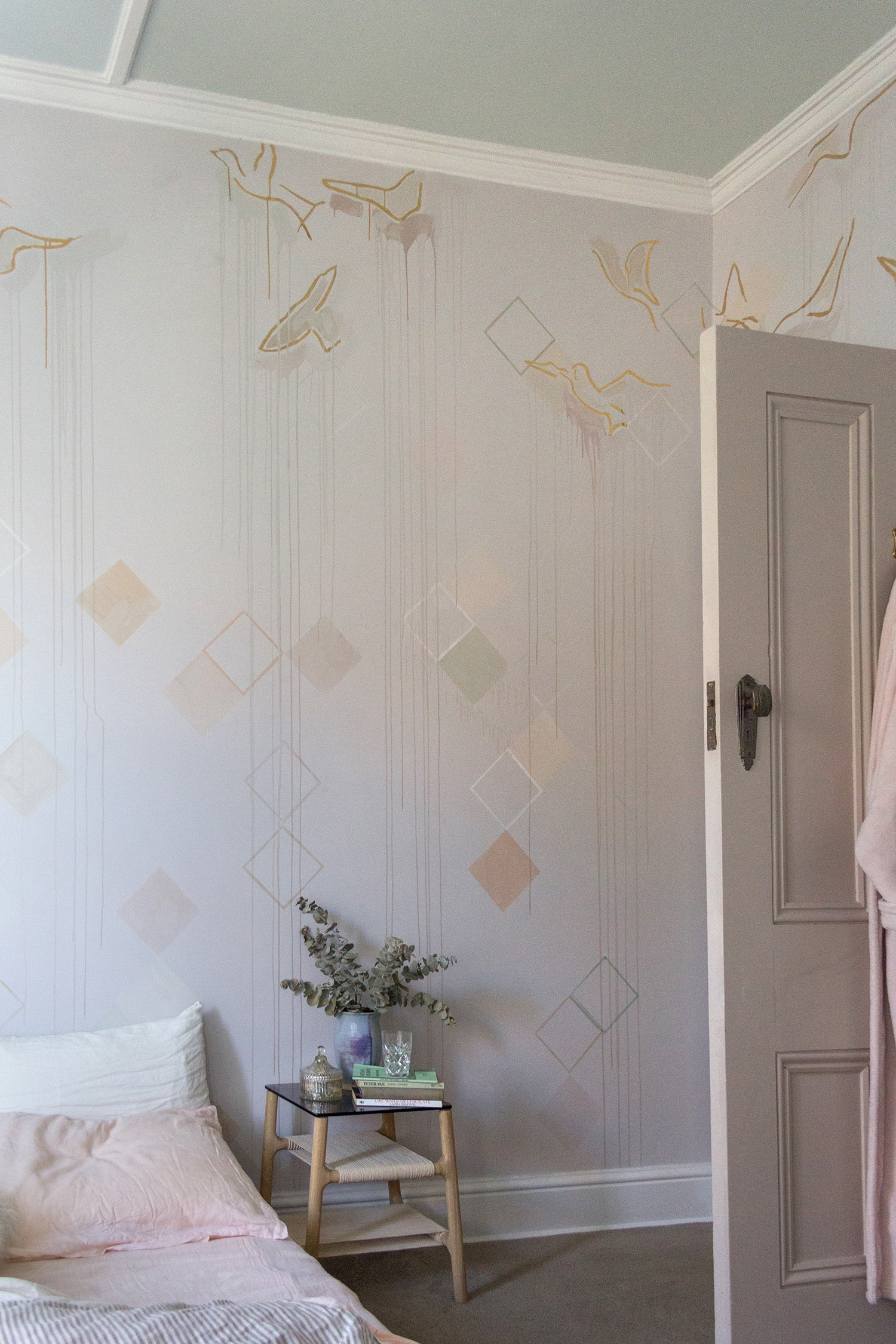 Pastel bedroom mural featuring geometric shapes, dripping paint and gold leaf birds flying. The bed is made with linen bedding and a soft, pink throw.
