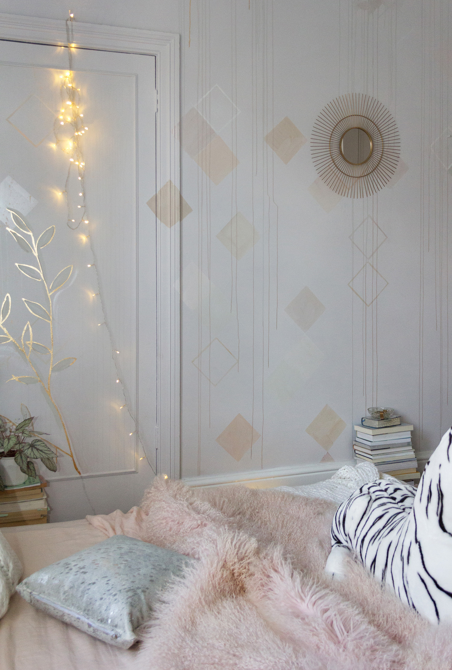 Pastel bedroom mural featuring geometric shapes and dripping paint. The bed is made with linen bedding and a soft, pink throw while fairy lights cast a magic glow.