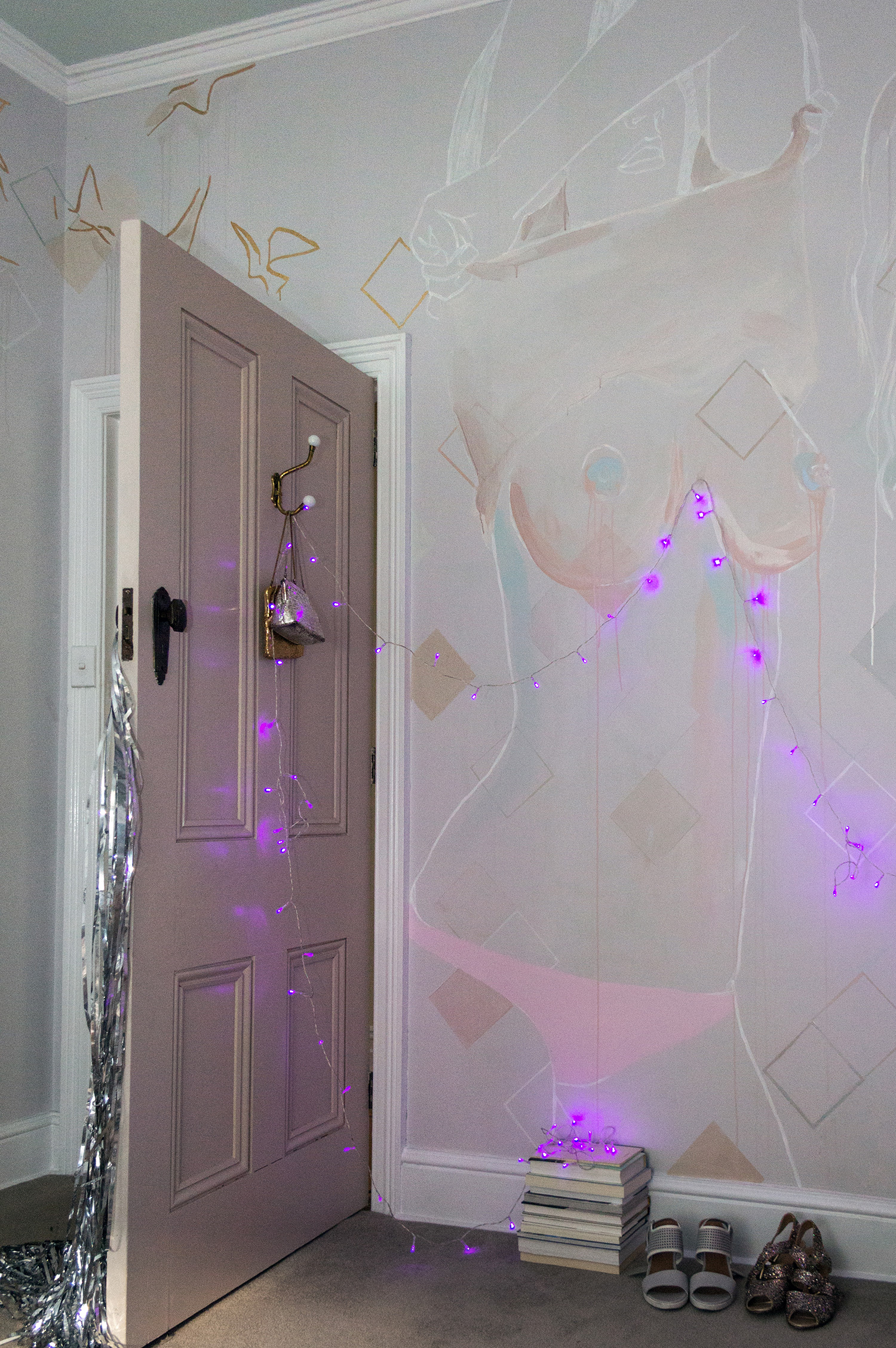 Topless woman mural - female is taking her top off and exposing her naked breasts. Painted in pastel and metallic colours with gold leaf birds flying out from the figure. Fairy lights hang under the woman's breasts and a silver metallic curtain hangs from the door handle.