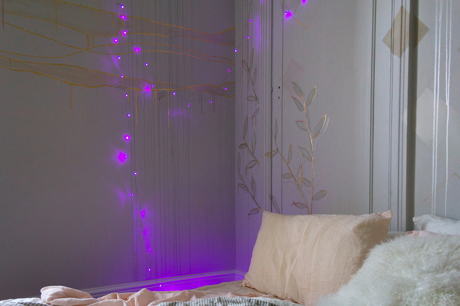 Gold leaf feature wall in cosy bedroom, the wall features waves and gold foliage lit up by purple fairy lights.