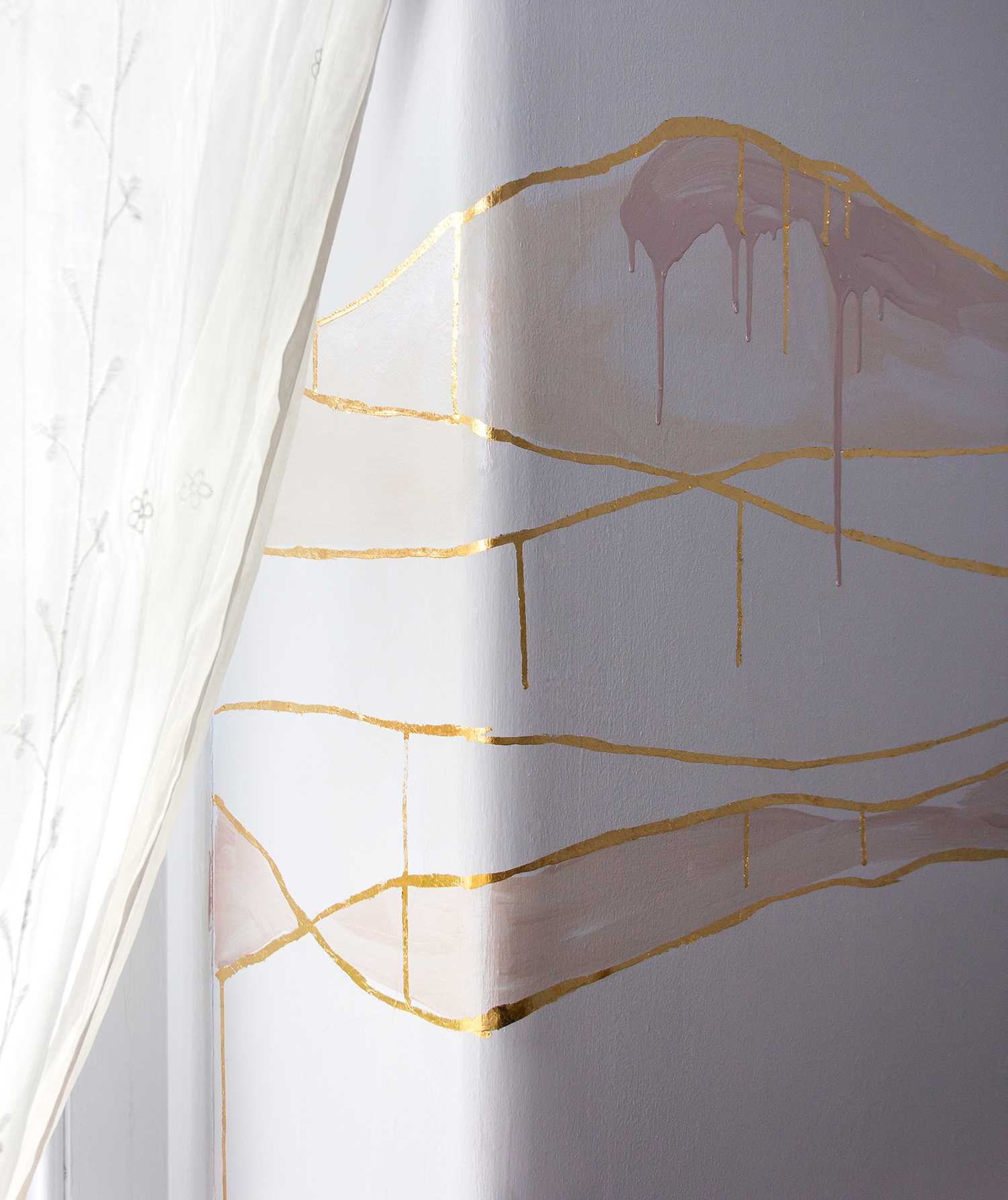 Close up gold leaf feature wall in cosy bedroom, the wall features wavy lines in gold and pink metallic paint. Light pours through a thin white curtain.