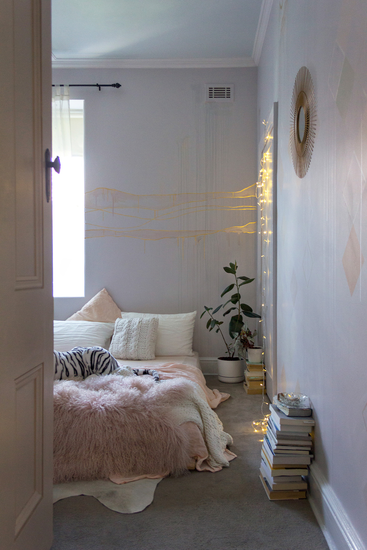 Gold leaf feature wall in cosy bedroom, the bed is made with peach linen sheets and a Mongolian sheepskin throw.