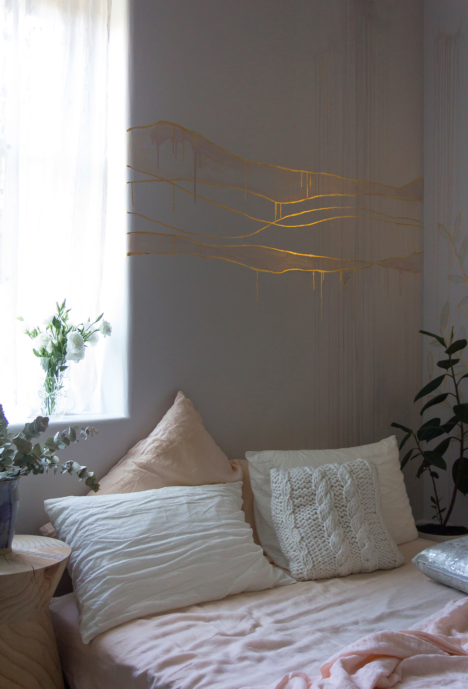 Gold leaf feature wall in cosy bedroom, the wall features wavy lines in gold and pink metallic paint. Light pours through a thin white curtain and plants surround the bed.