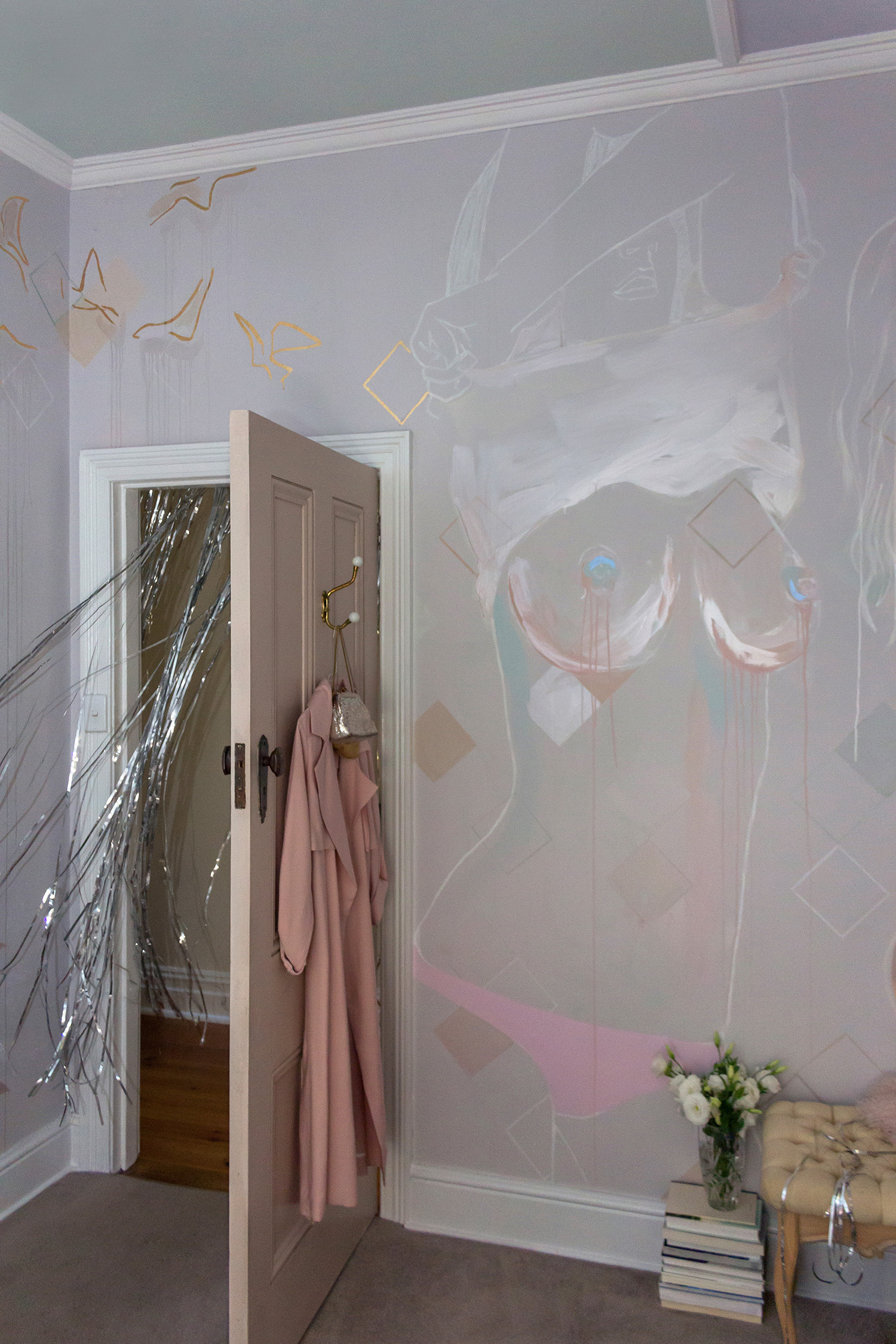 Topless woman mural - female is taking her top off and exposing her naked breasts. Painted in pastel and metallic colours with gold leaf birds flying out from the figure. A sparkly silver curtain hangs from the doorway.