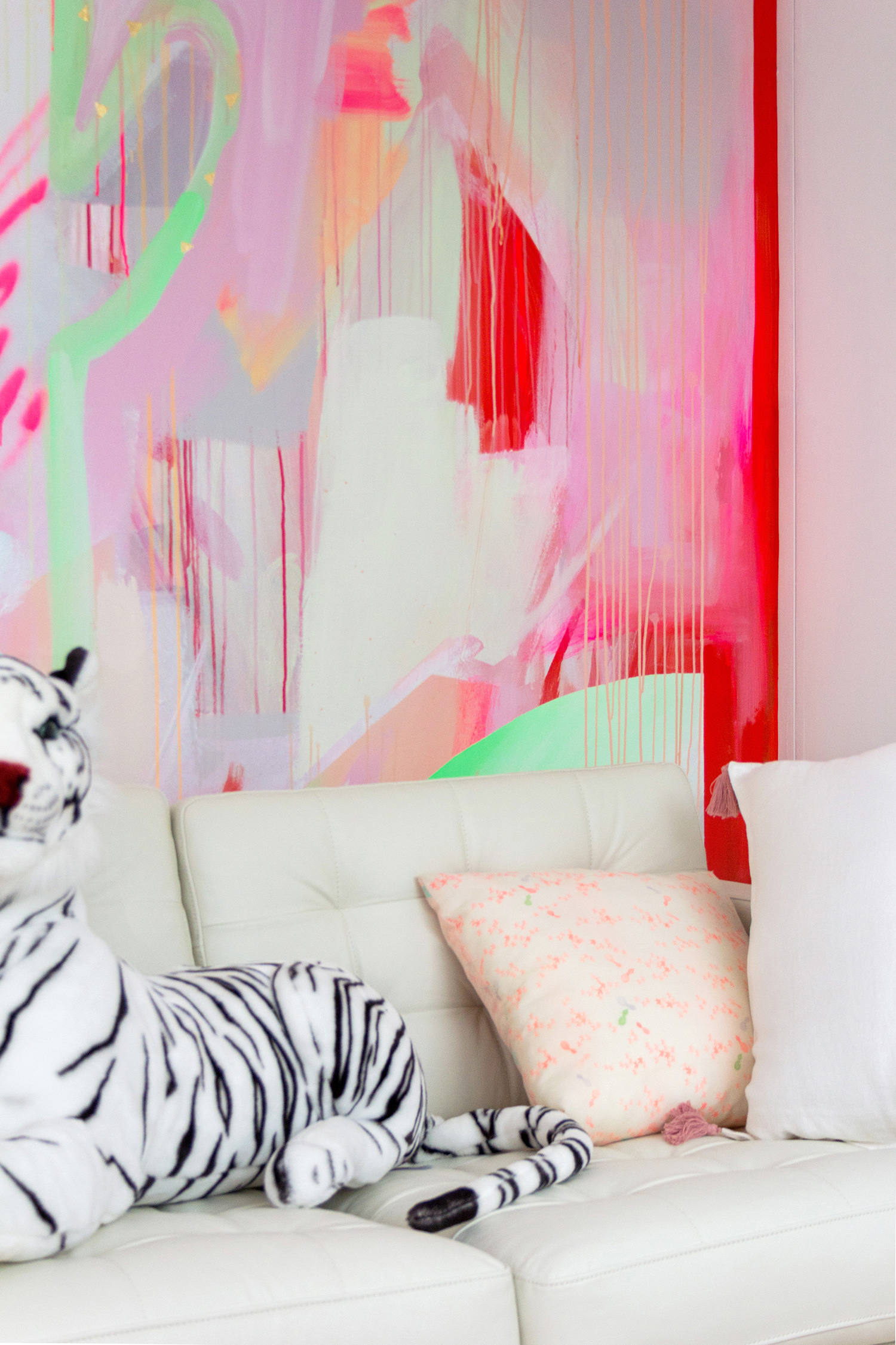 Vibrant wall mural in bright neon colours, features a spray painted cactus. Styled in front is a white leather couch and black and white toy tiger.