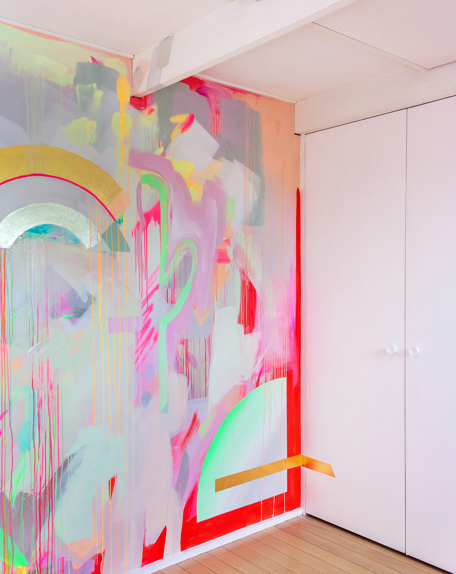 Vibrant wall mural in bright neon colours, features a spray painted cactus, gold leaf accents and metallic rainbow.