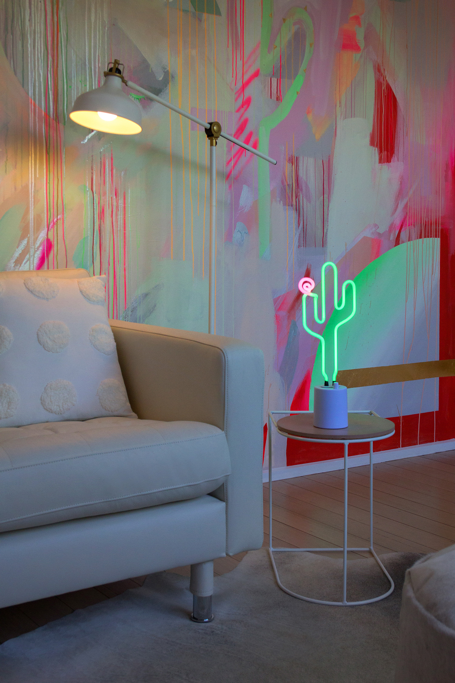 Vibrant galaxy wall mural in bright neon colours, featuring gold leaf shapes and spray painted cactus. Styled in front is a white leather couch and neon cactus lamp.