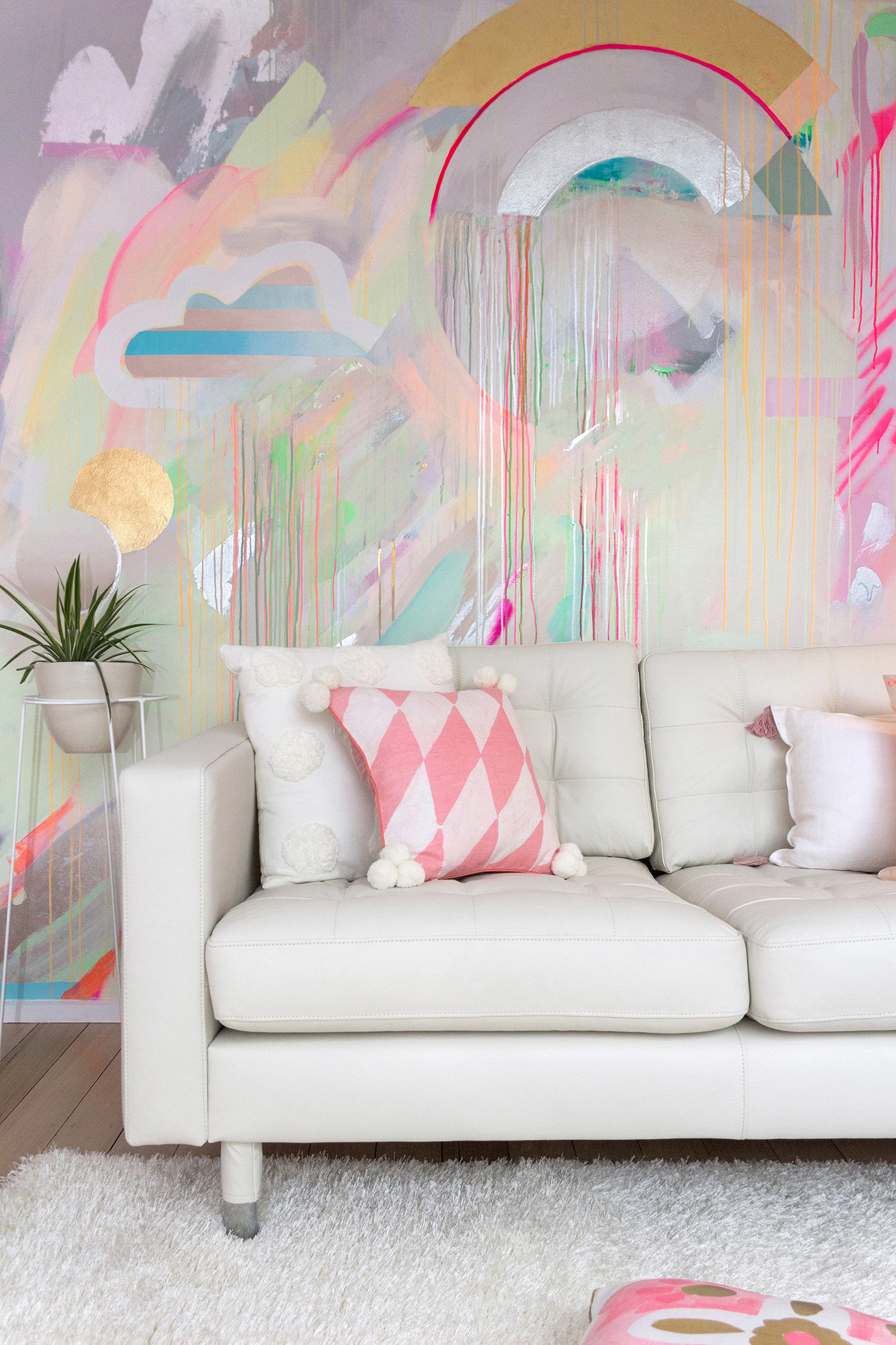 Vibrant galaxy wall mural in bright neon colours, featuring gold leaf shapes, metallic rainbow and striped cloud. Styled in front is a white leather couch and Bonnie and Neil cushions.