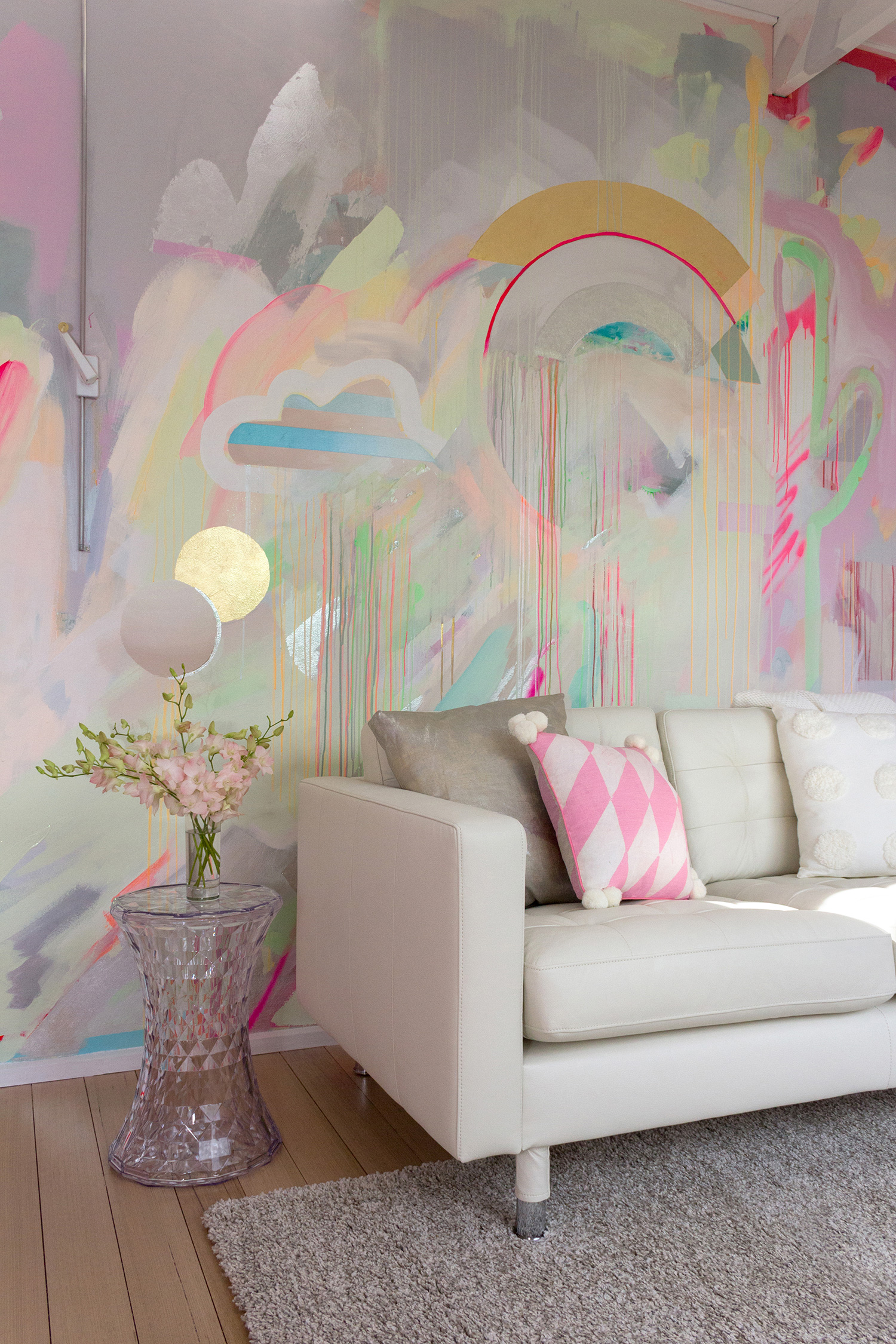 Vibrant galaxy wall mural in bright neon colours, featuring gold leaf shapes, metallic rainbow, spray painted cactus and striped cloud. Styled in front is a white leather couch and prism side table with a vase of flowers.