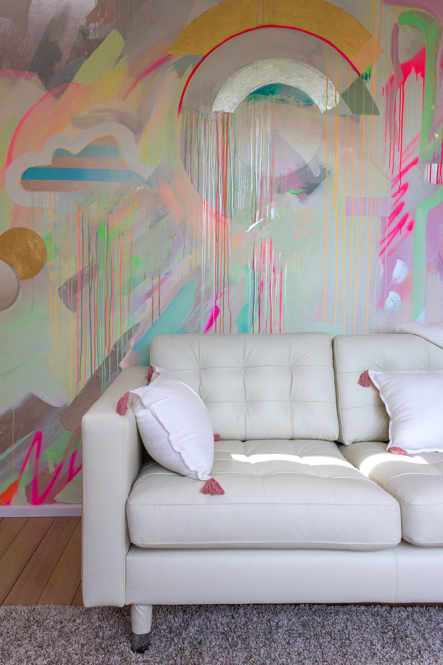 Vibrant galaxy wall mural in bright neon colours, featuring gold leaf shapes, metallic rainbow, spray painted cactus and striped cloud. Styled in front is a white leather couch and cushions.