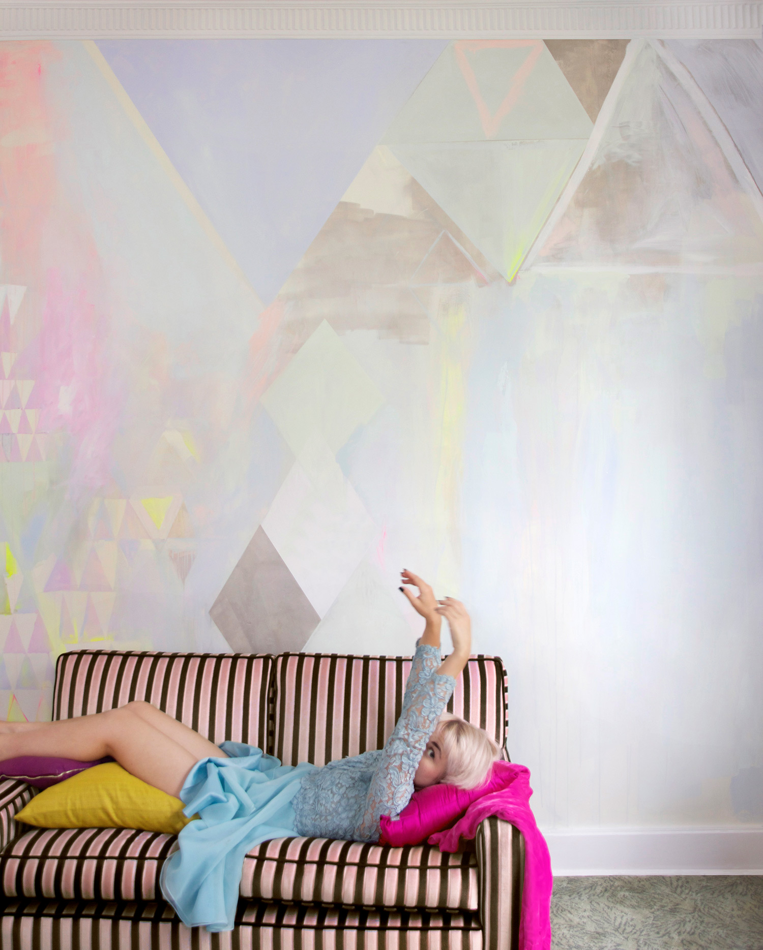 Diamond abstract pastel mural with metallic paint and neon yellow highlights, featuring vintage striped velvet couch with model lounging in pastel blue lace vintage dress and cheekily peering at camera.