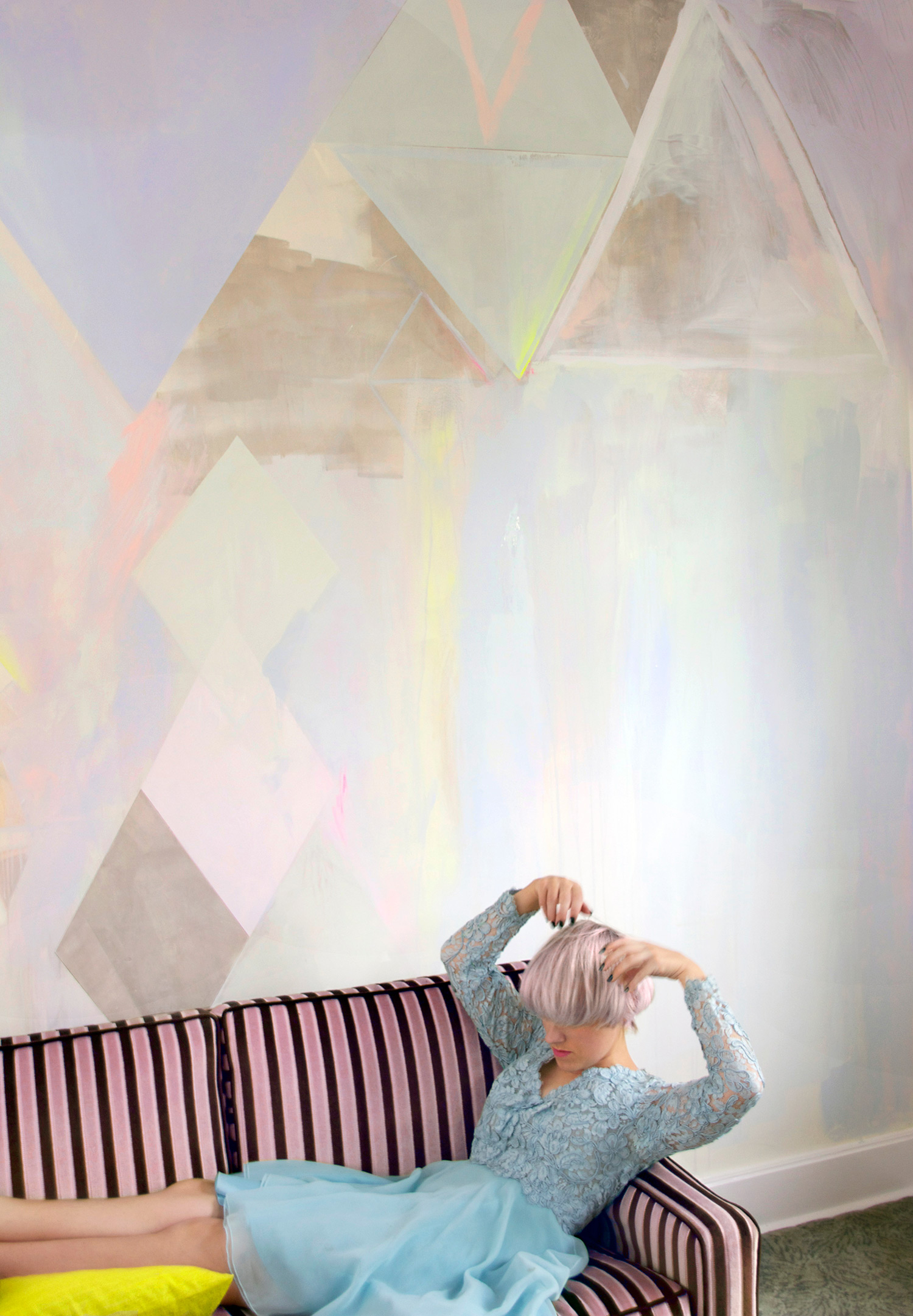 Diamond abstract pastel mural with metallic paint and neon yellow highlights, featuring vintage striped velvet couch with model playfully lounging in pastel blue lace vintage dress and cropped hair.