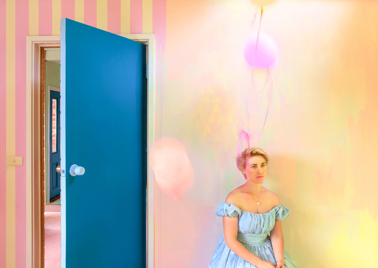 Alice in Wonderland theme styled interior featuring pastel abstract mural, candy striped walls, balloons and portrait of Alice seated staring wistfully off camera, wearing off the shoulder blue princess dress and short blonde hair.