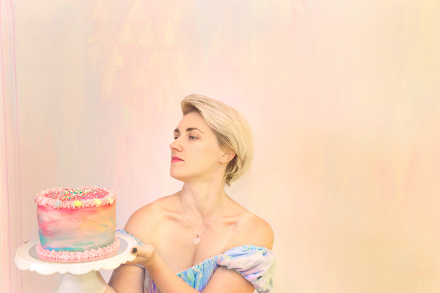 Alice in Wonderland party theme styled interior featuring pastel abstract mural and portrait of Alice carrying a rainbow layer cake with sprinkles, wearing off the shoulder blue princess dress and short blonde hair.