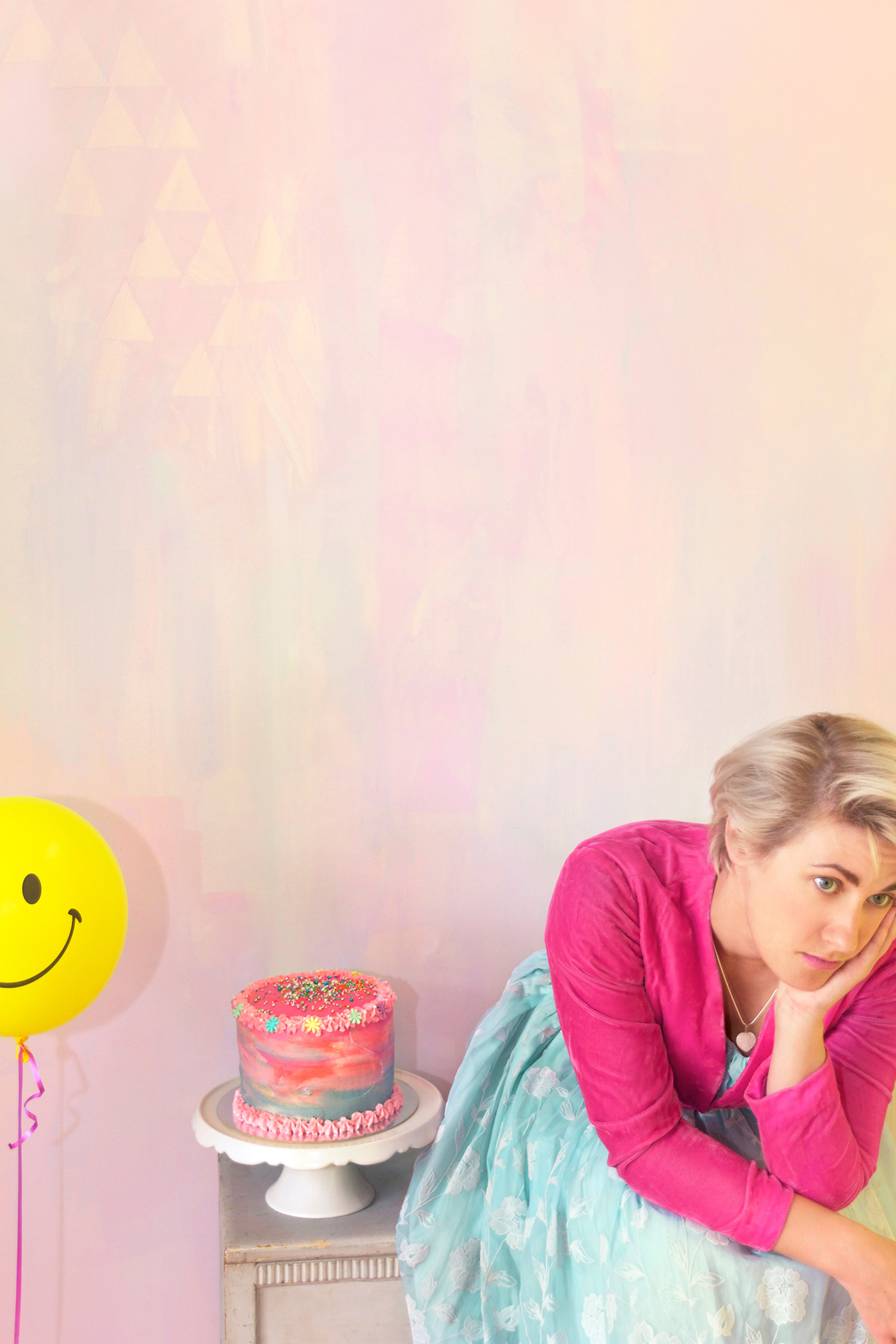 Alice in Wonderland party theme styled interior featuring pastel abstract mural and portrait of Alice wearing blue princess dress and pink cropped jacket, featuring rainbow layer cake with sprinkles and smiley face yellow helium balloon.