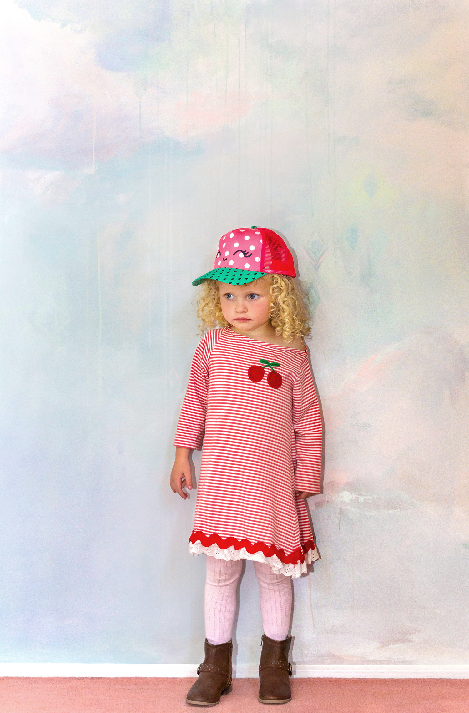 Dreamily styled children's bedroom idea, with painted cloud mural in pastel tones, features blonde curly haired child model wearing stripey cherry red dress.