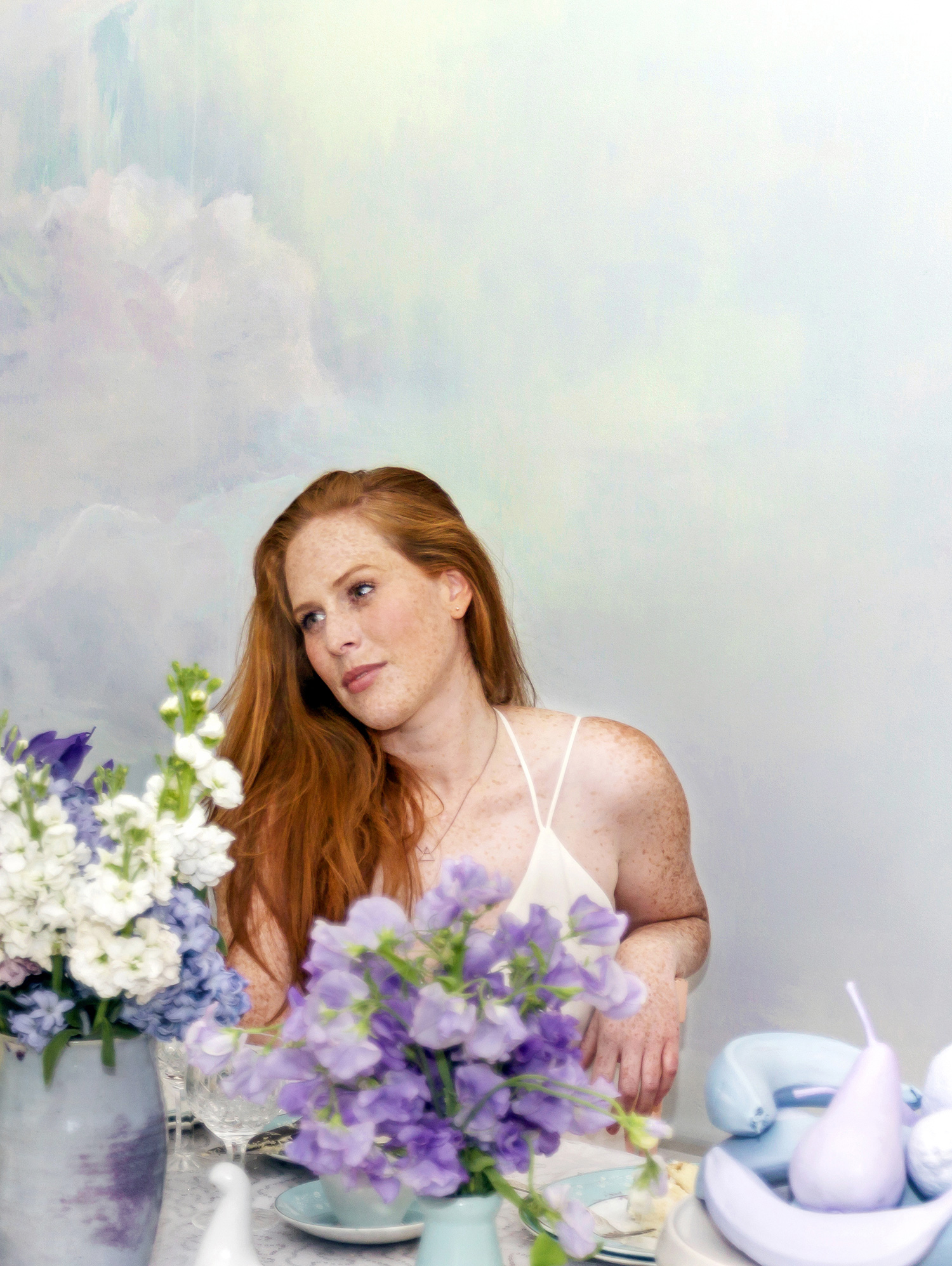 Dreamily styled dinner party in the clouds, with painted cloud mural in pastel tones, red haired model seated at table stares wistfully, the table features flowers, porcelain doves and an iced vanilla layer cake.