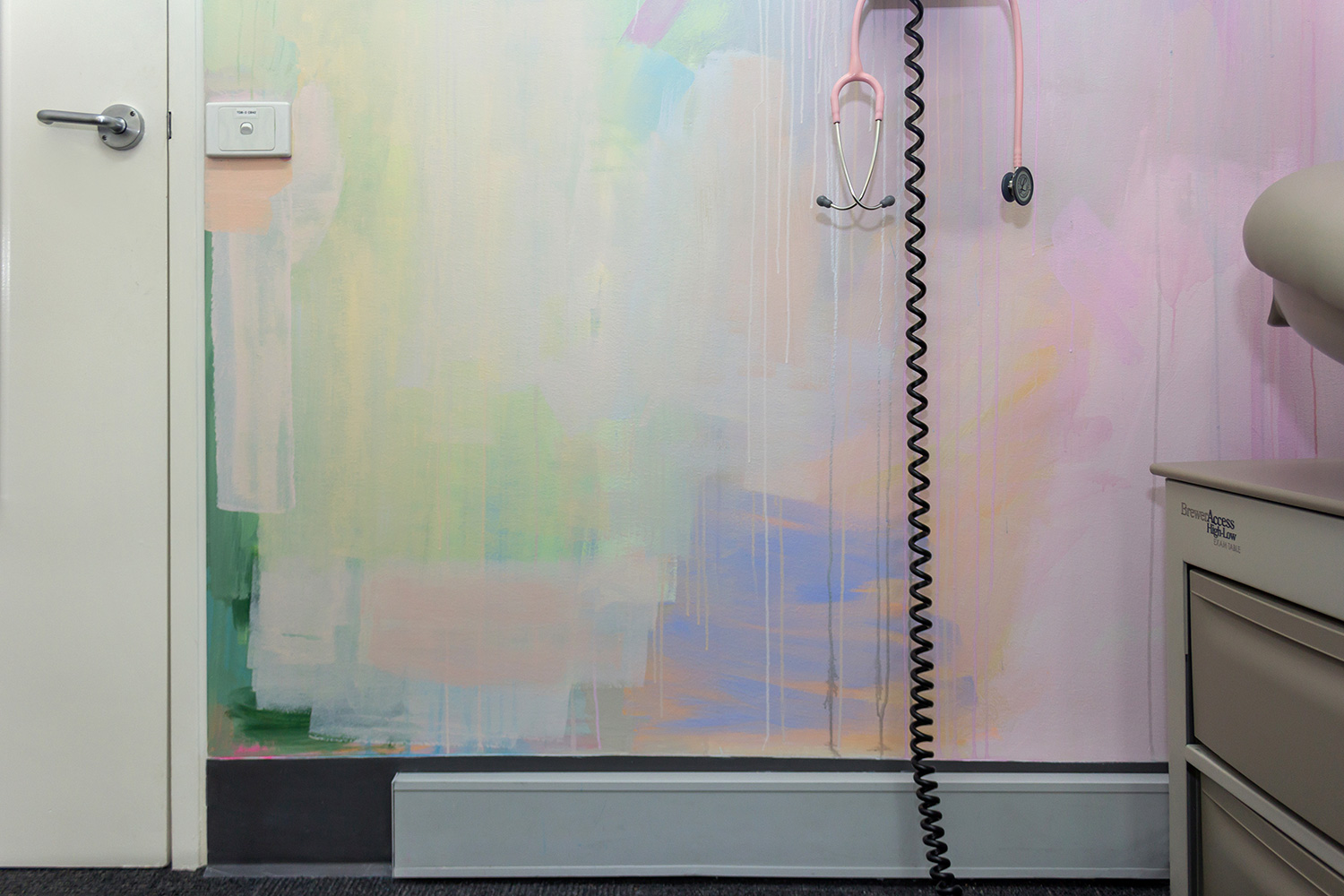 Close up of pastel abstract mural painted in an OB/GYN office, featuring pink stethoscope, medical equipment and paint details.