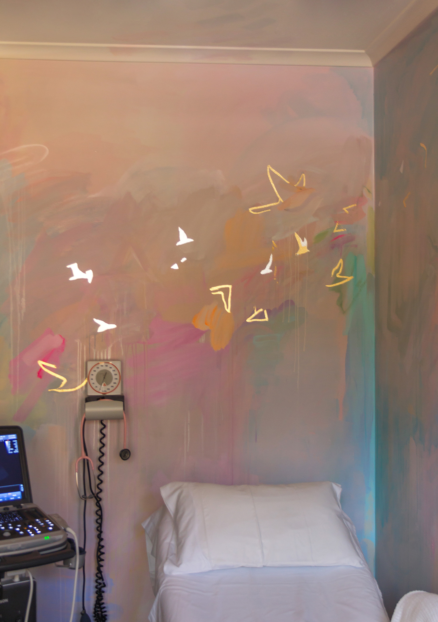Pastel abstract mural painted in an OB/GYN office, featuring pink stethoscope and medical equipment. Room has a soft pink glow, gold and silver gilded birds and geometric shapes fly across the wall.